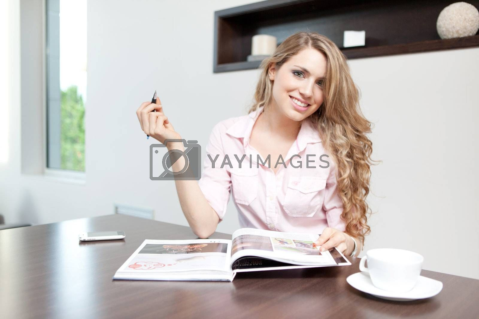 young beautiful woman smiling with printed catalog and pen