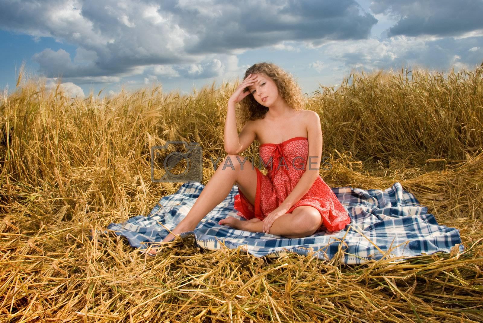 Beautiful slavonic girl on picnic in wheat field