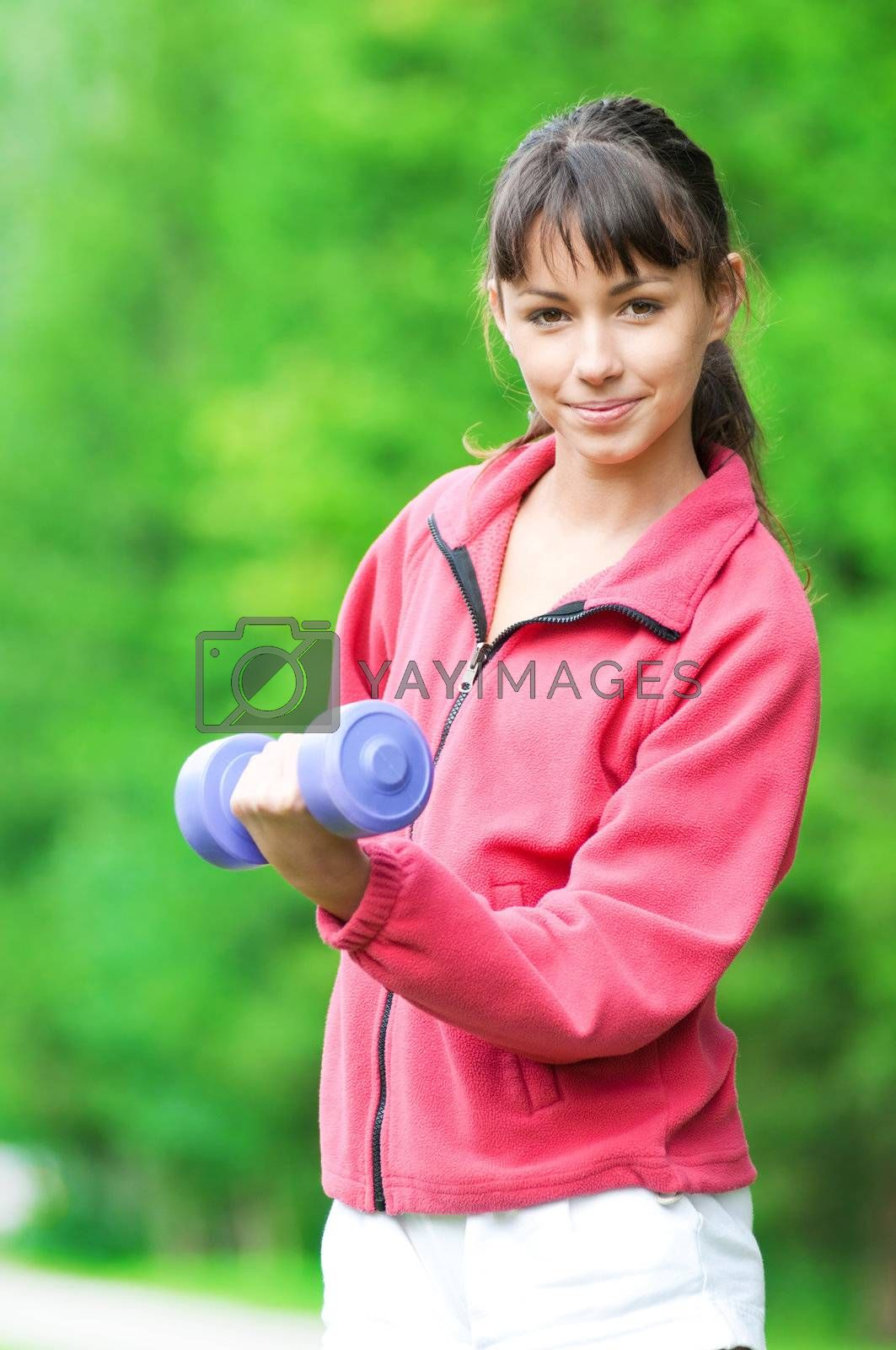 Beautiful teenage girl doing dumbbell exercise on green grass at park