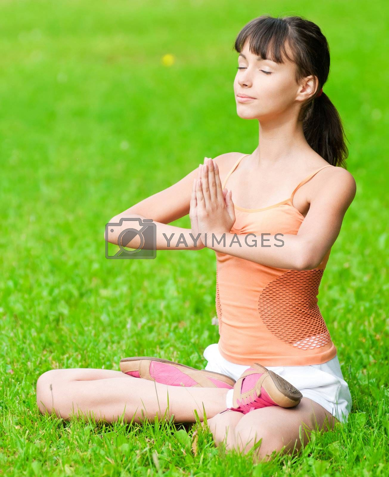 Beautiful teenage girl doing stretching exercise on green grass at park. Yoga