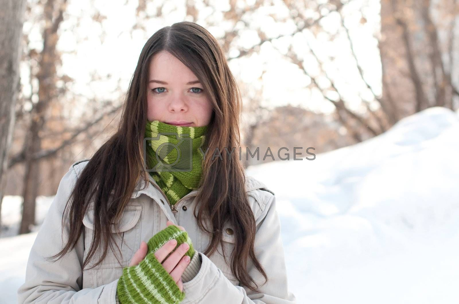 Winter lifestyle. Beautiful girl with green scarf and gloves over snow landscape
