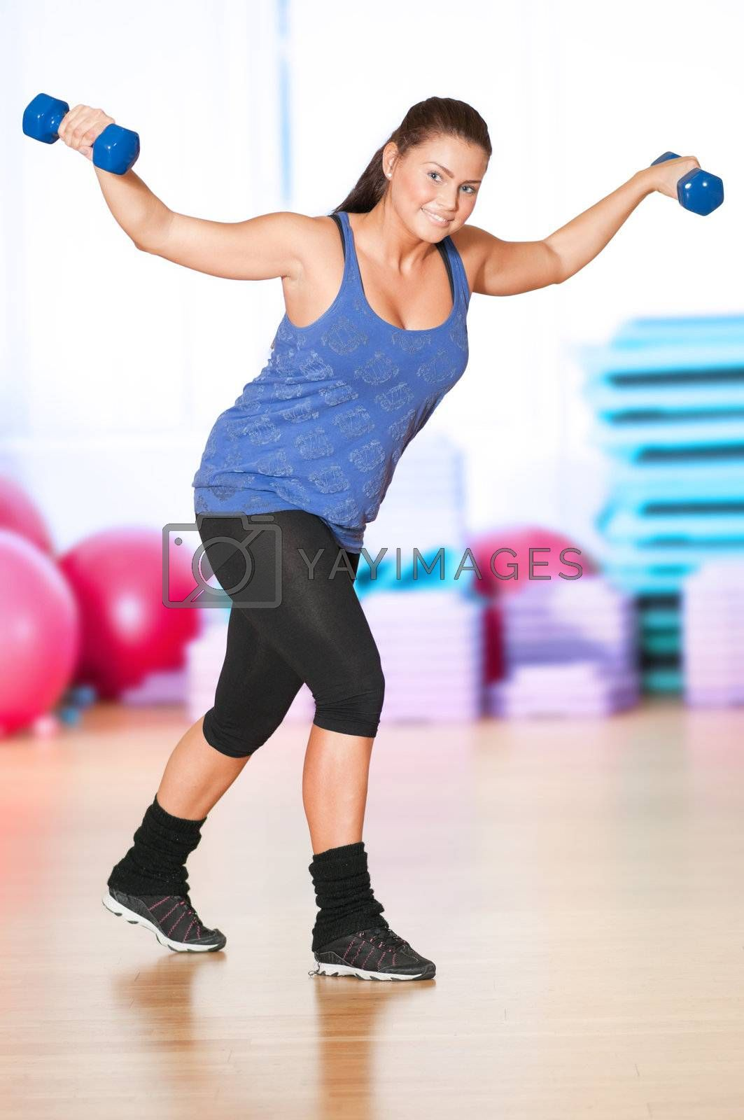 Woman doing fitness exercise at sport gym by markin