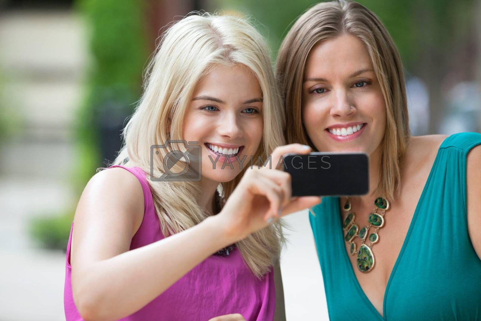 Happy young female friends taking selfportrait with cellphone