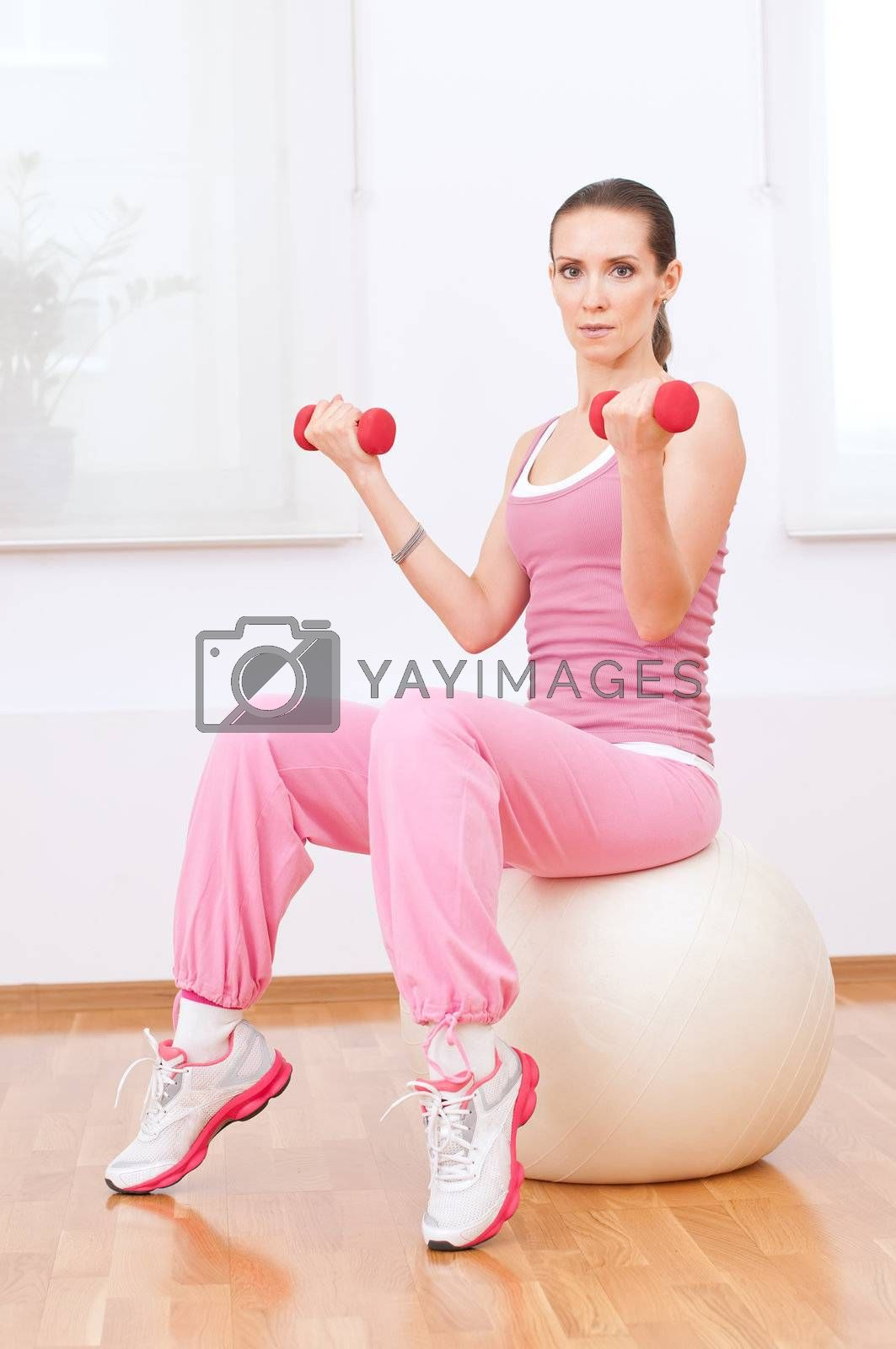 Woman doing dumbbell exercise at sport gym by markin