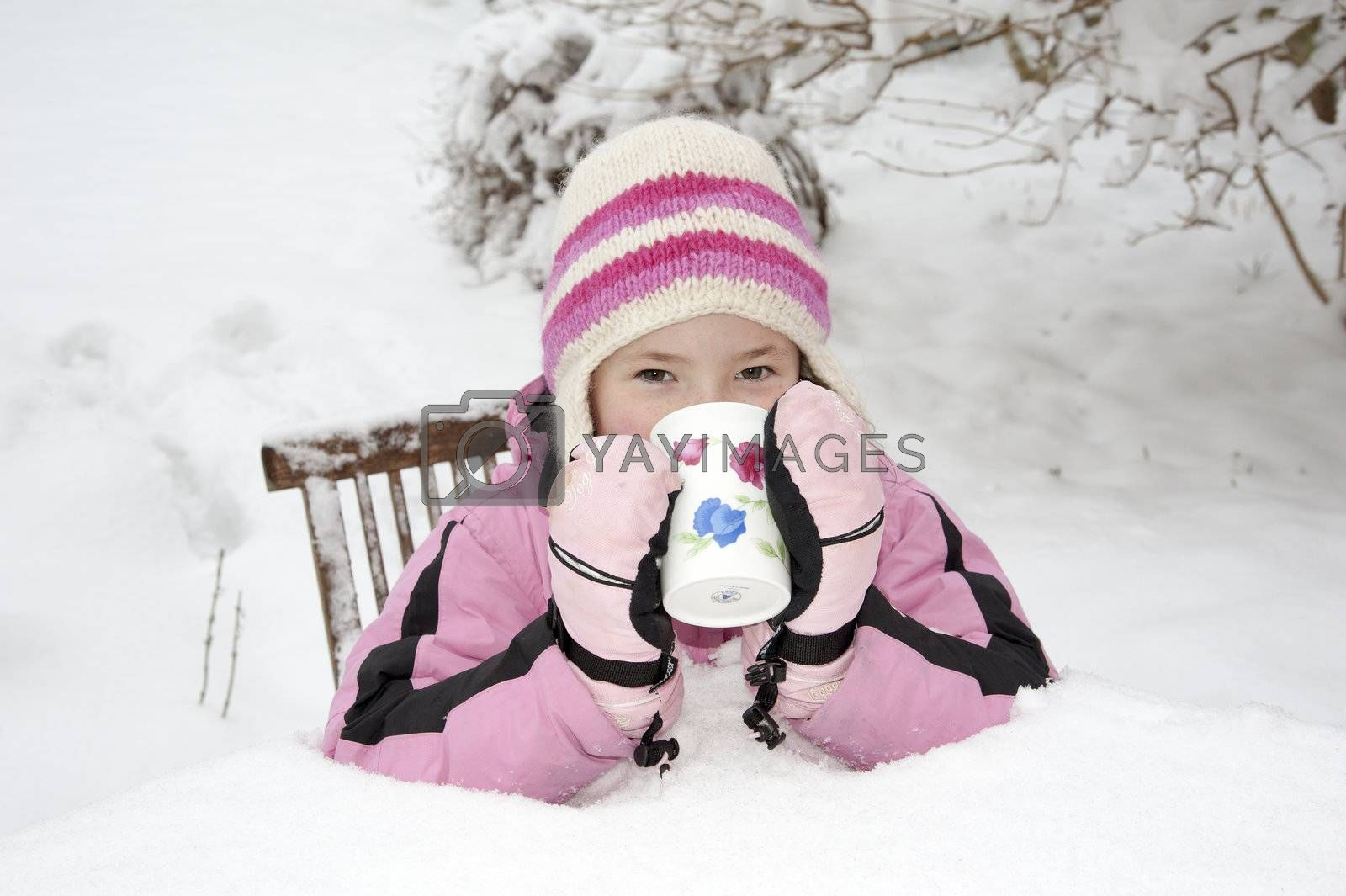 Winter snow in Hampshire UK and this little girl takes a break from snowballing for a hot drink seated on a garden chair