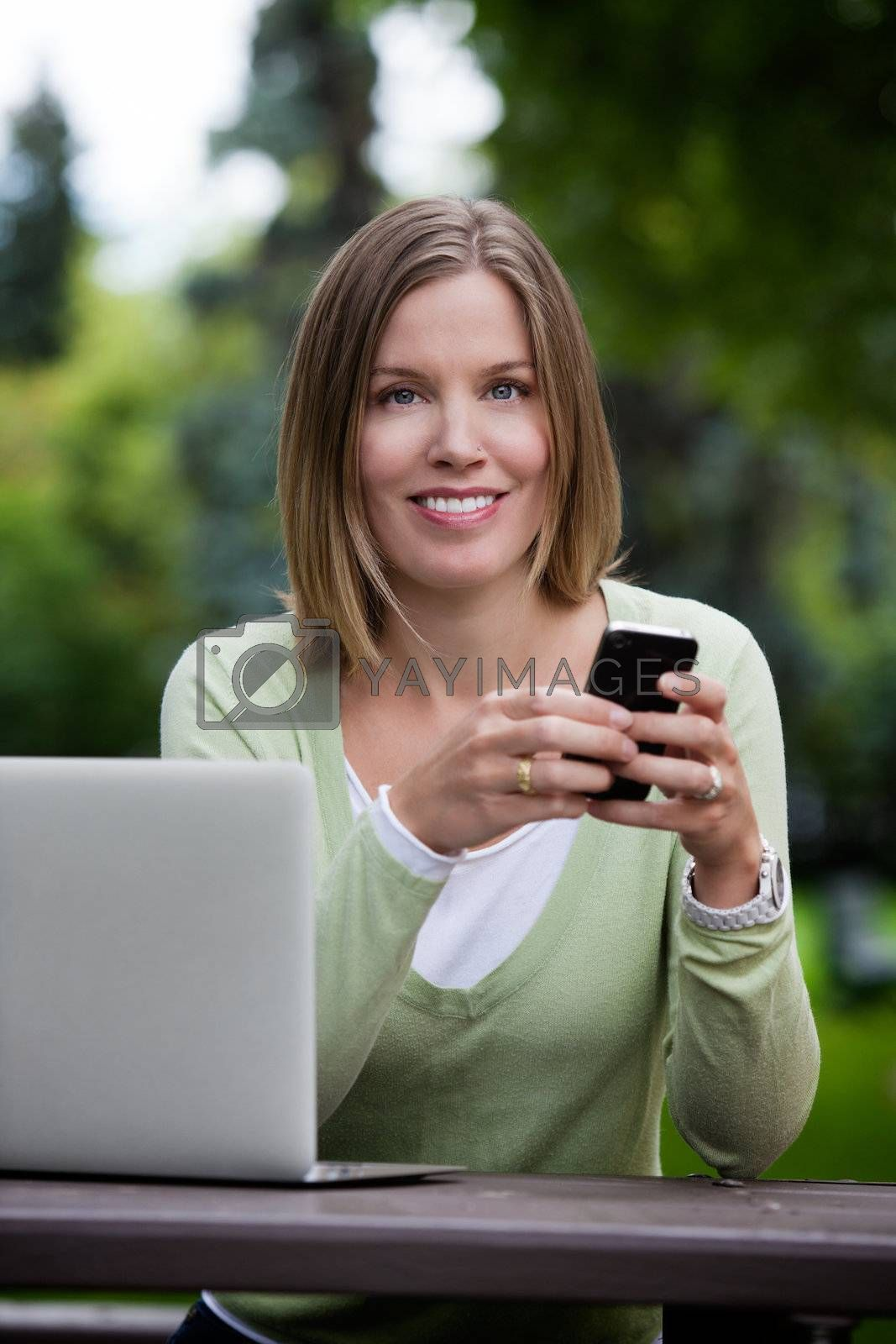 Attractive young adult in park with smart phone writing message