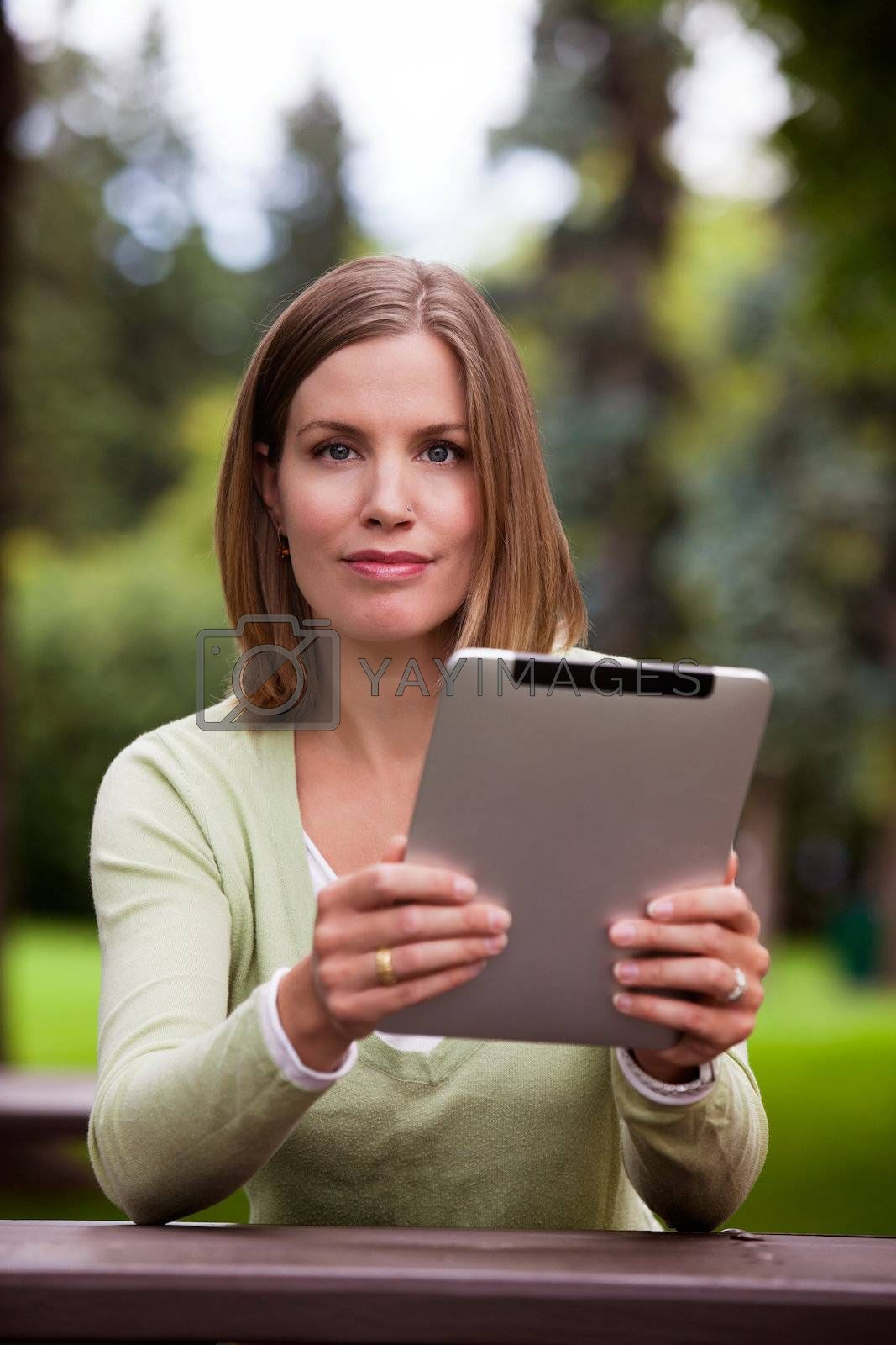Portrait of attractive young woman in park holding digital tablet