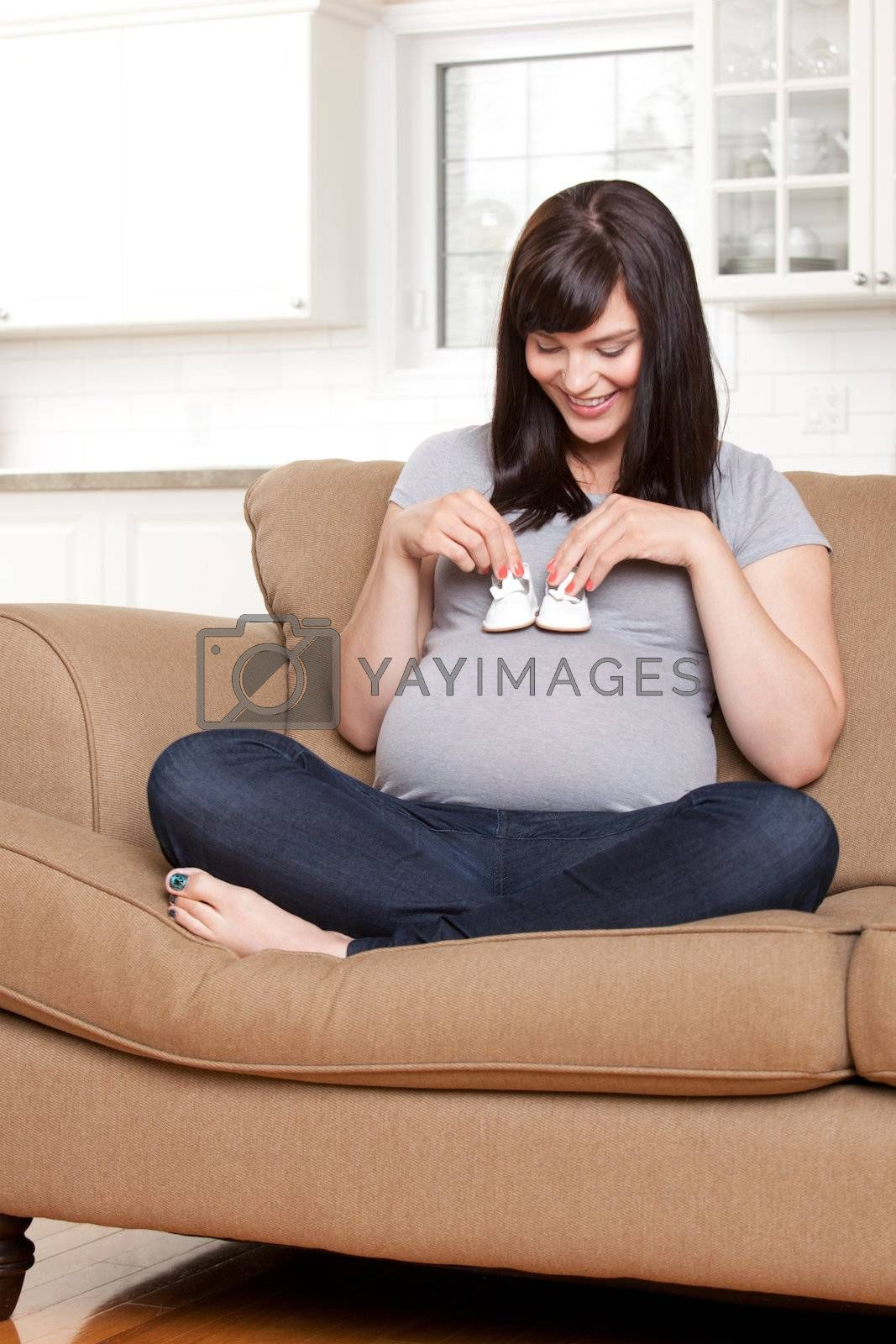 Portrait of a happy young pregnant woman holding baby shoes on belly