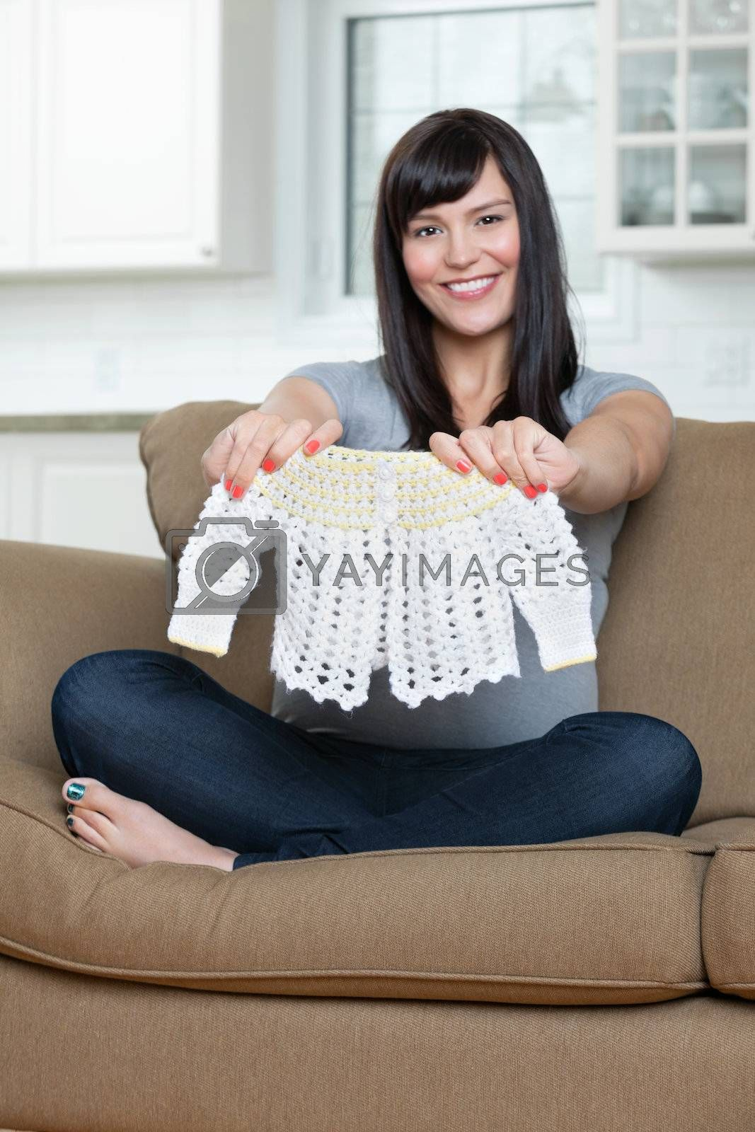 Portrait of happy pregnant woman holding baby clothing while sitting on sofa
