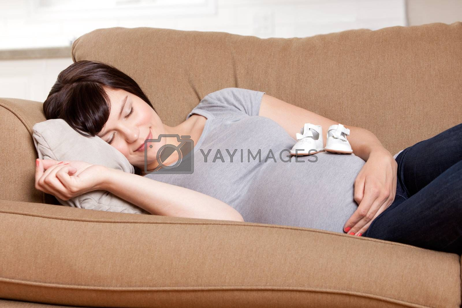 Content pregnant mother resting on sofa in living room with baby shoes on belly