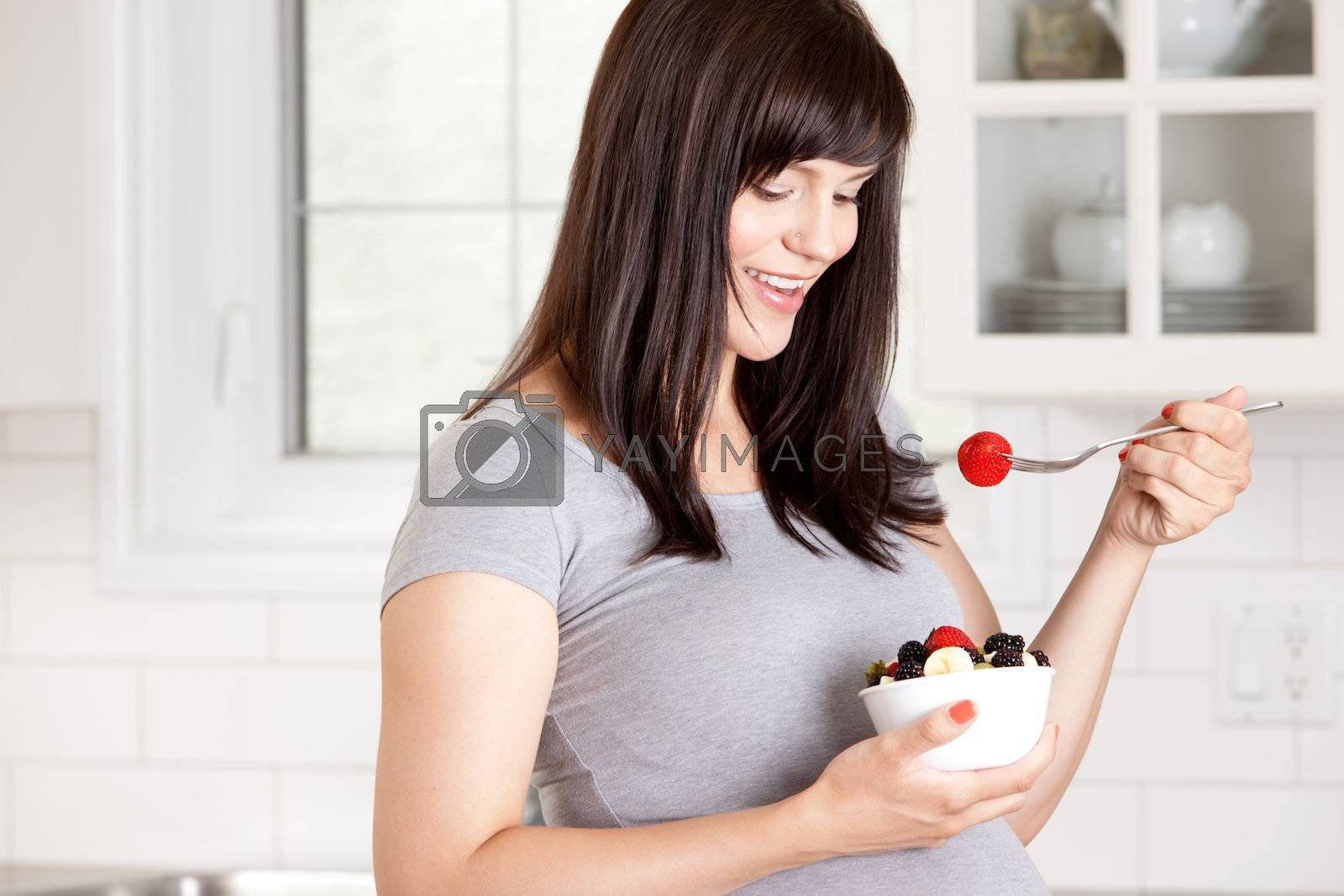 Happy pregnant woman eating healthy bowl of fresh fruit