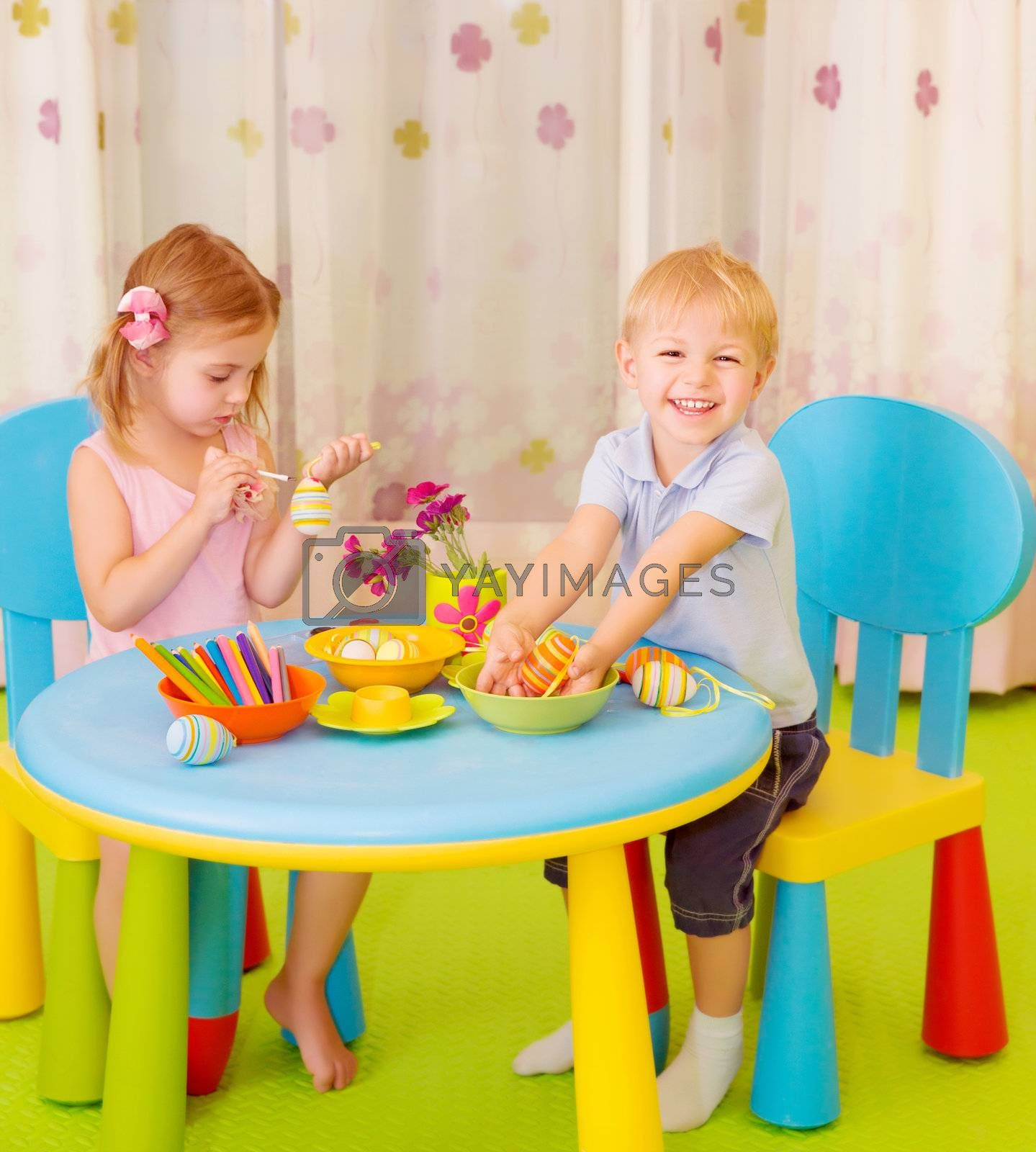 Royalty free image of Happy kids paint Easter eggs by Anna_Omelchenko