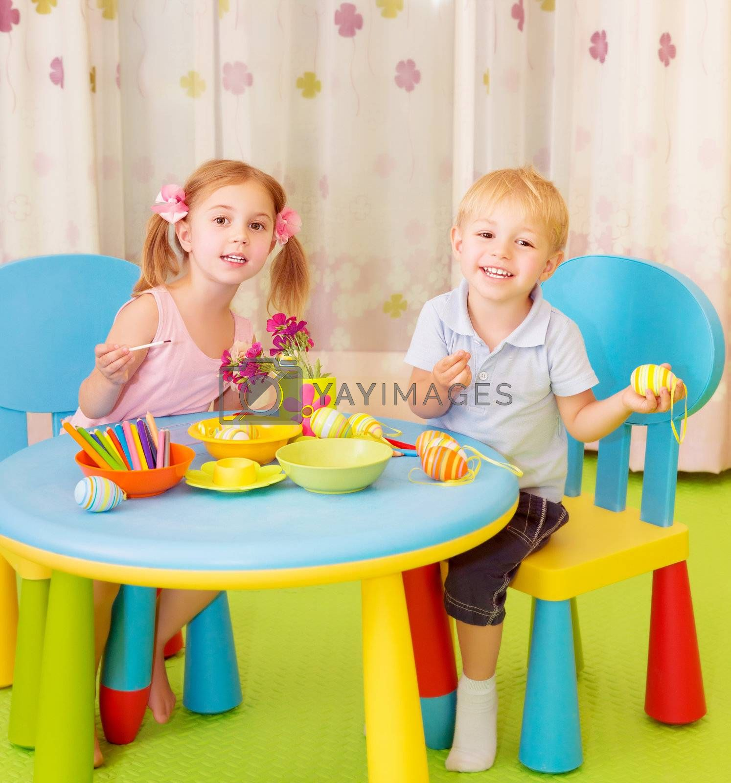 Two cheerful kids paint Easter eggs at home, handmade festive decorations, spring holiday, happiness concept