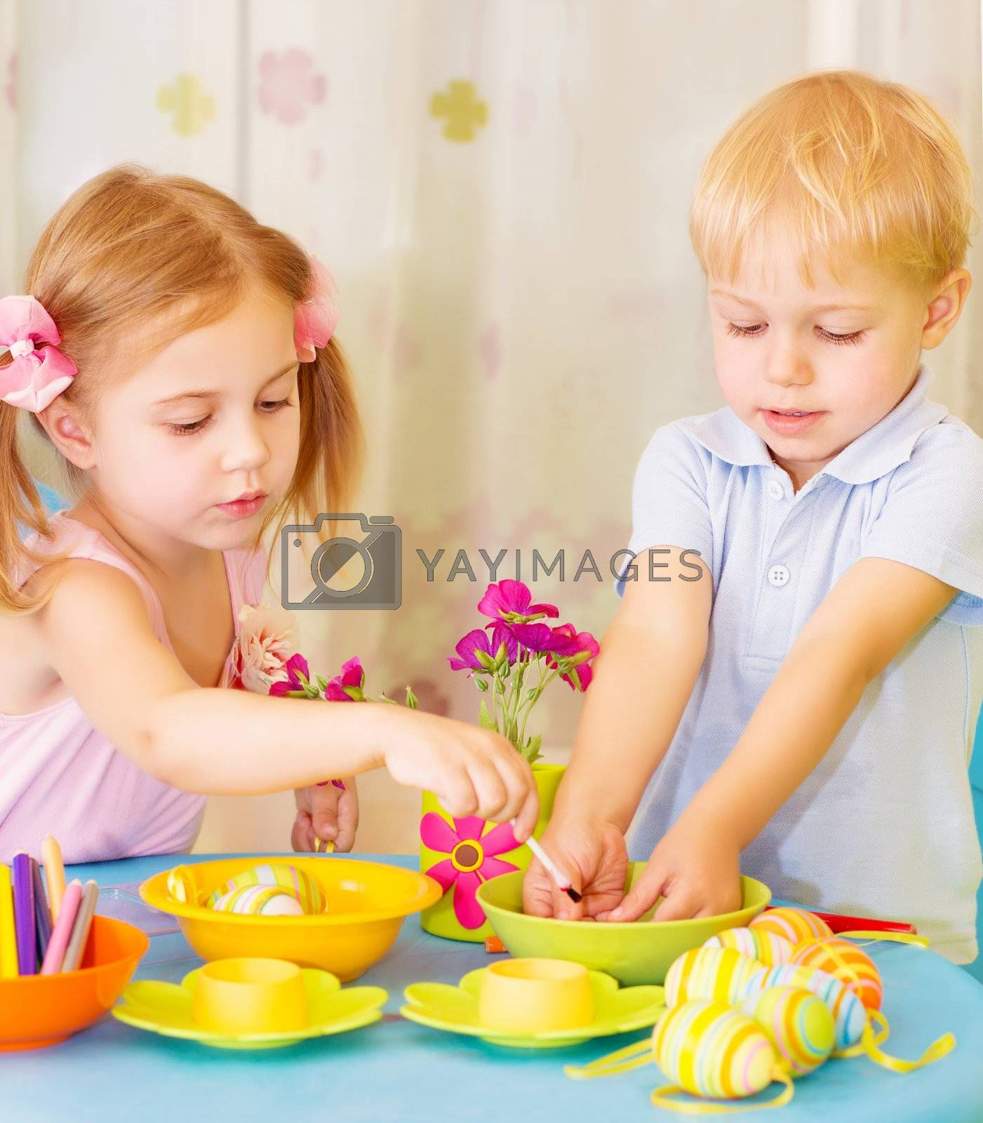 Two serious children paint Easter eggs at home, using colorful decoration, Christian holiday concept