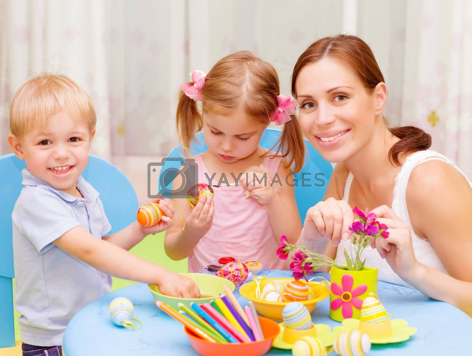 Two sweet toddler with young drawing teacher paint colorful Easter eggs, art lesson, handmade festive decor