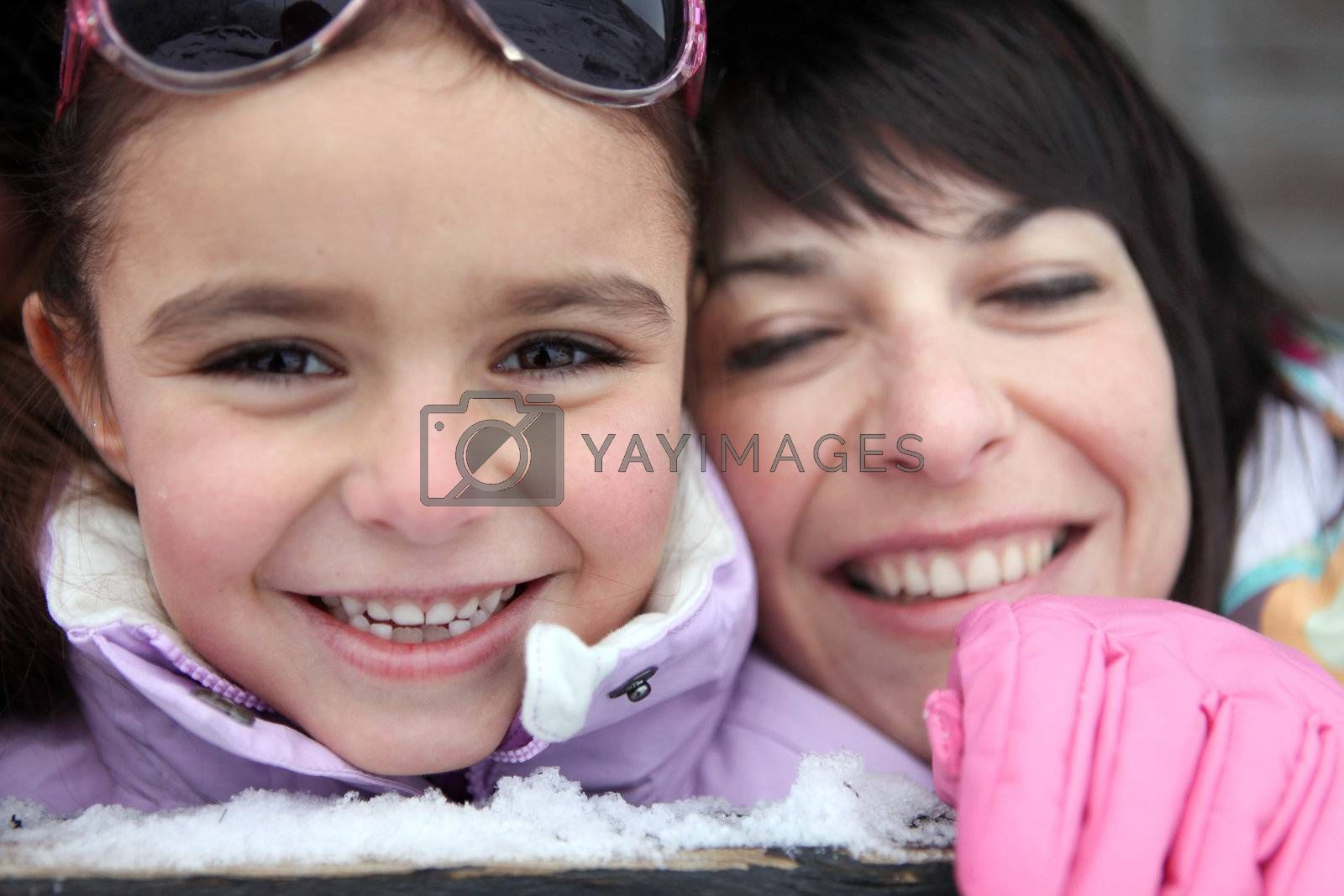 Mother and daughter giggling in the snow by phovoir