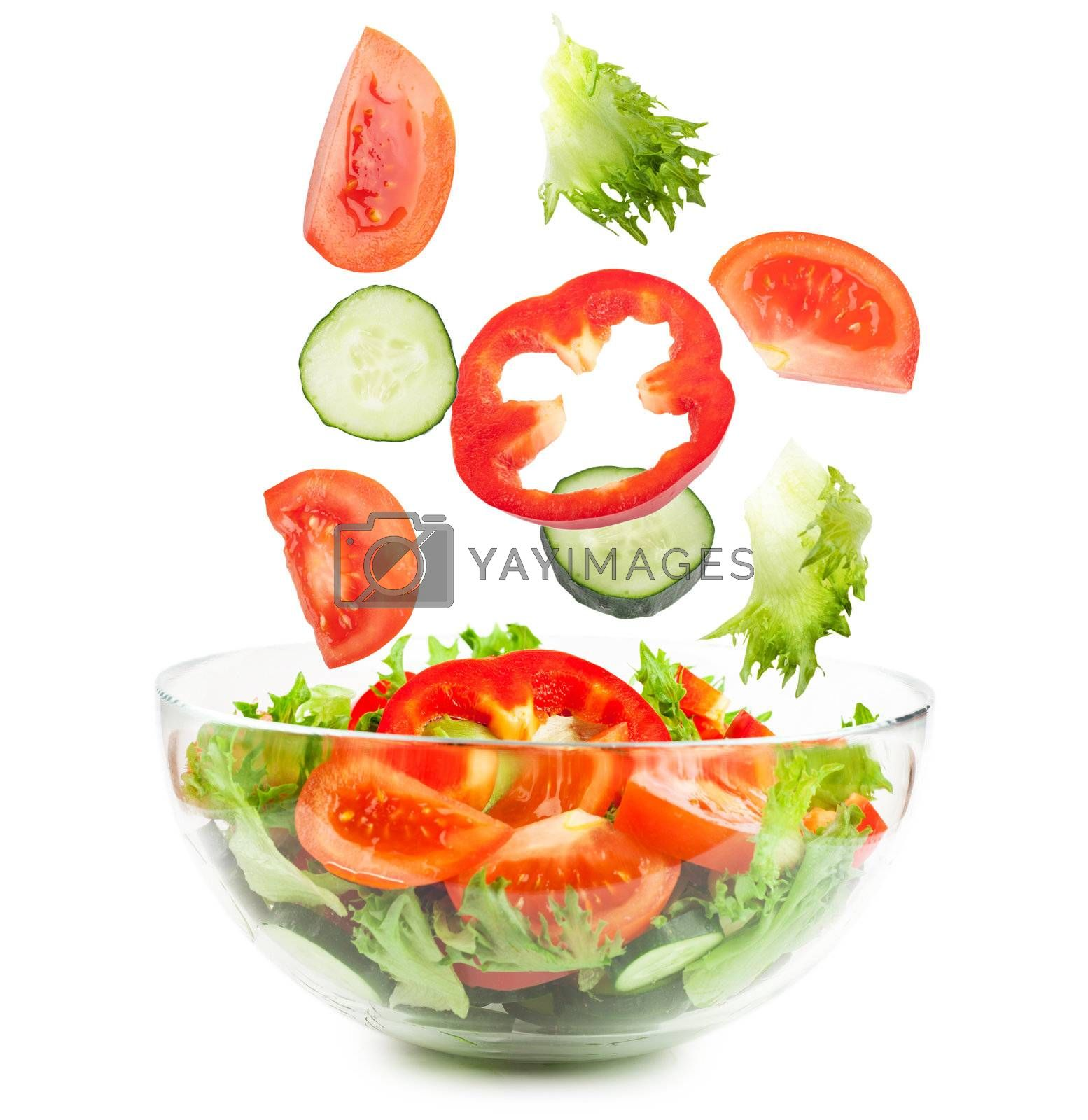 Fresh vegetables falling into the glass bowl isolated over white background