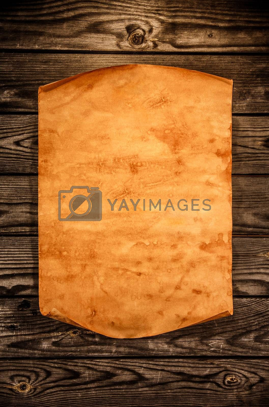 Blank old paper with curled edge against the background of an aged wood