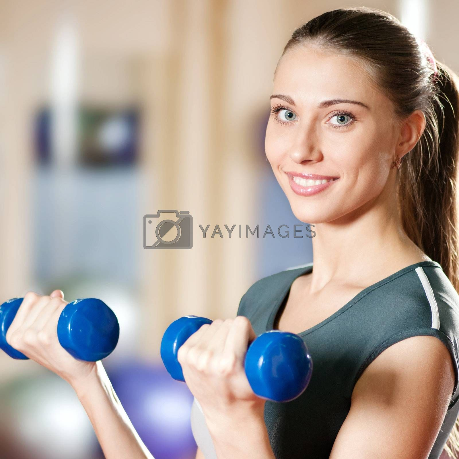 Beautiful sport woman doing power fitness exercise by markin