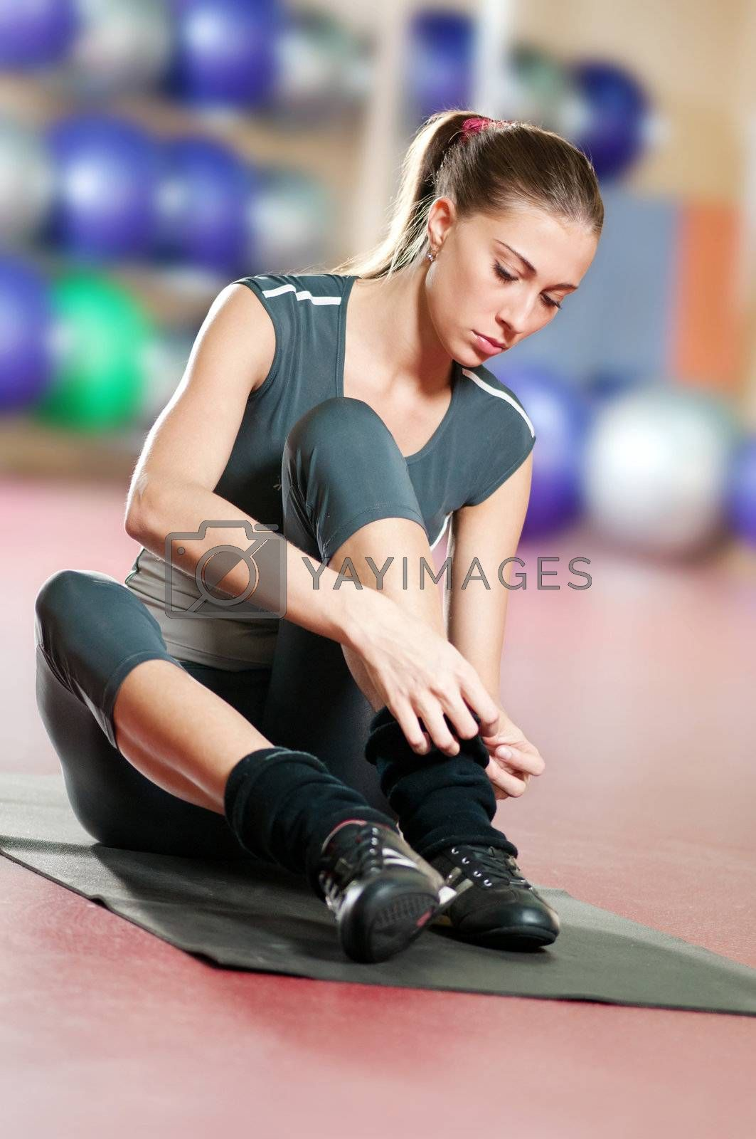 Woman doing stretching fitness exercise at sport gym. Yoga by markin
