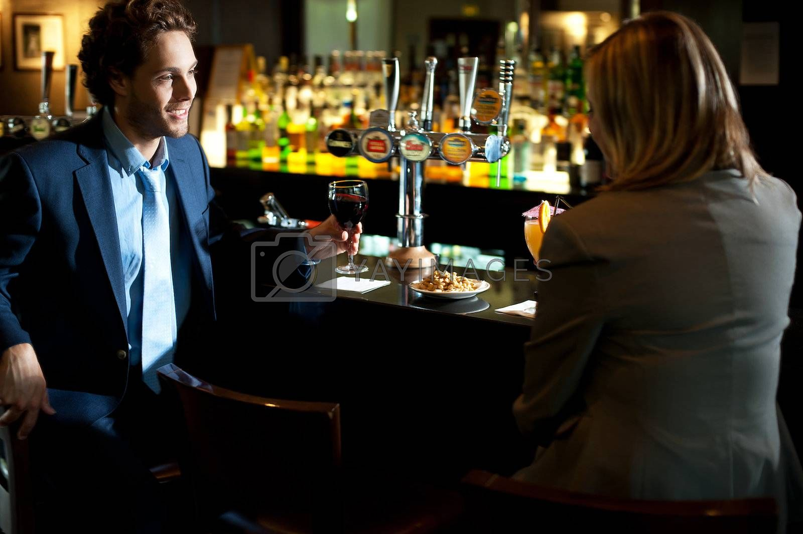 Attractive couple refreshing themselves at the bar. Enjoying drinks