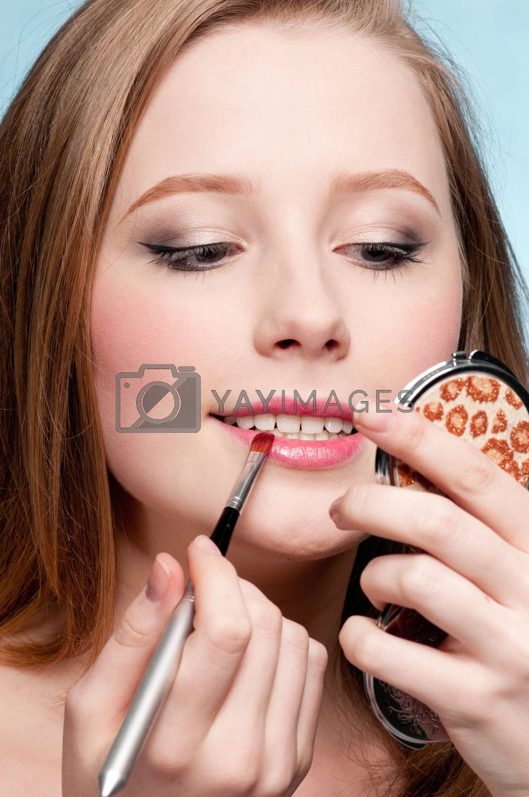 Beautiful young adult woman applying cosmetic lipstick brush - close-up portrait