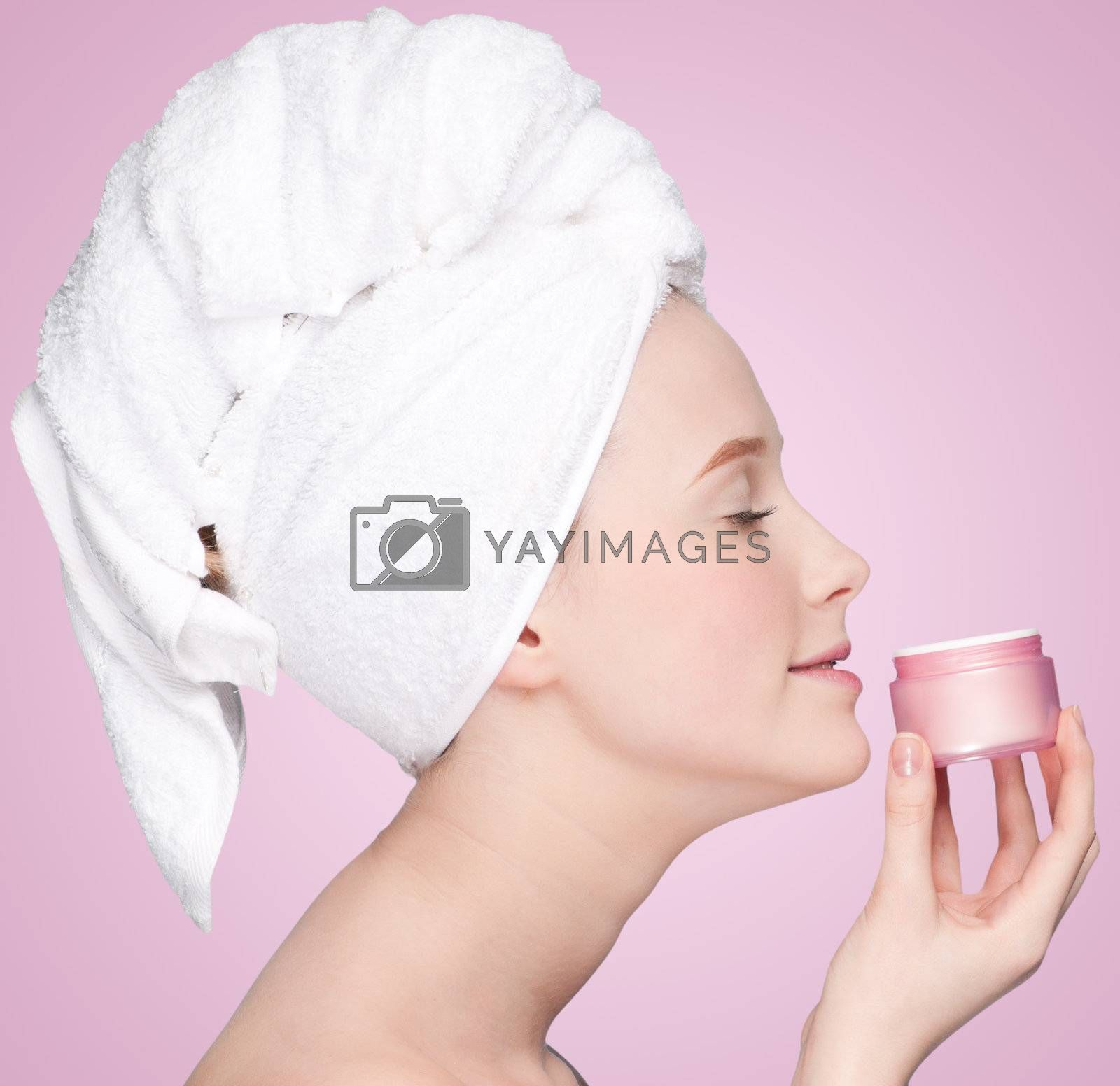 Beautiful woman smell jar of moisturizer cream. Close-up fresh young woman face