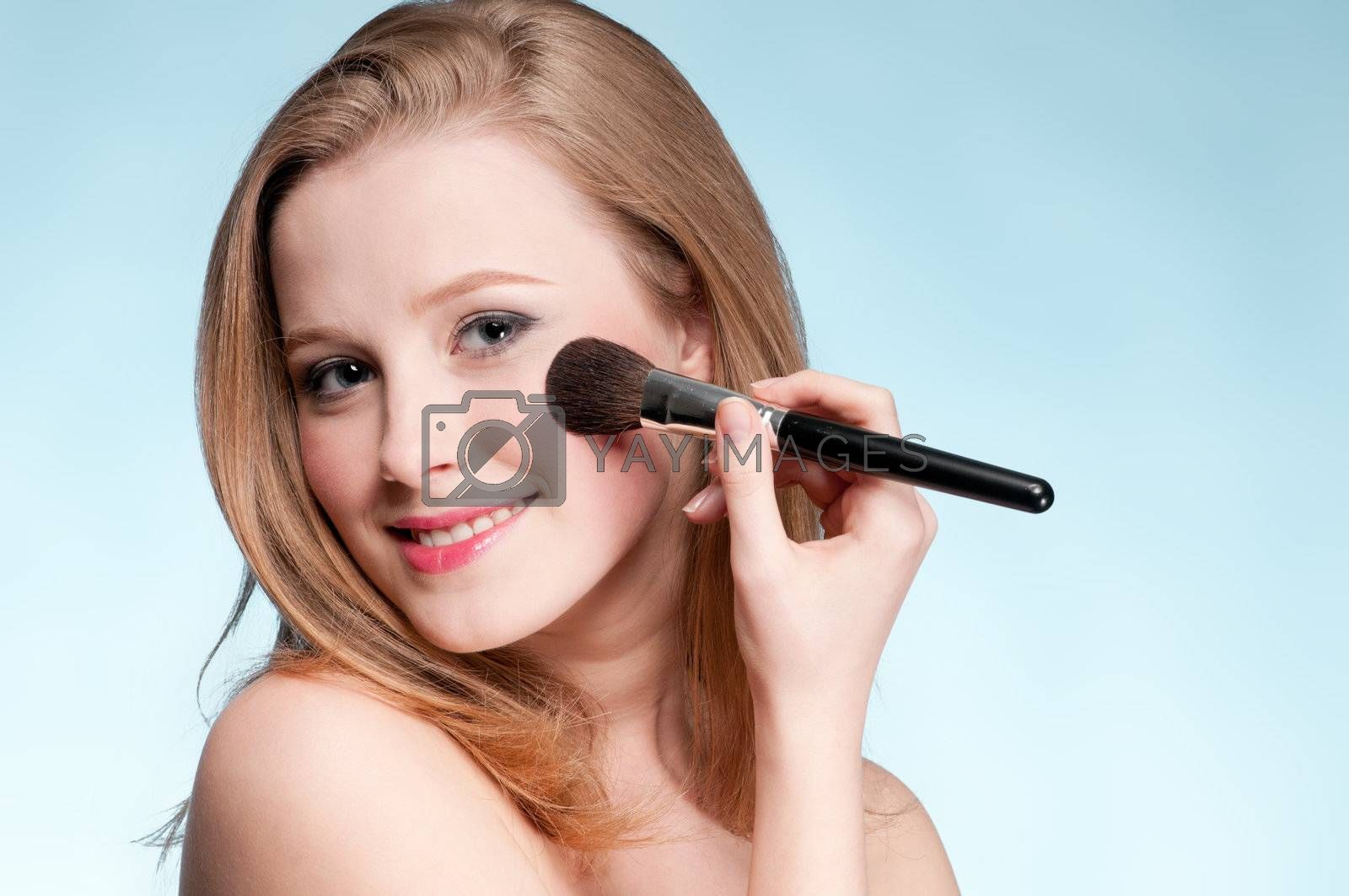 Beautiful young adult woman applying cosmetic paint brush - close-up portrait