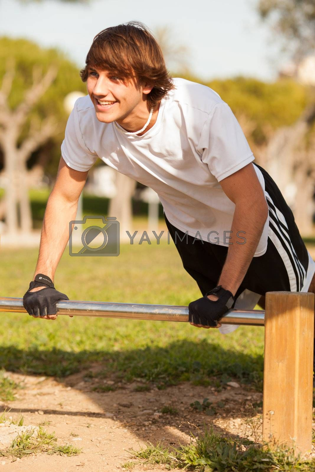 young healthy man making exercise in a public park