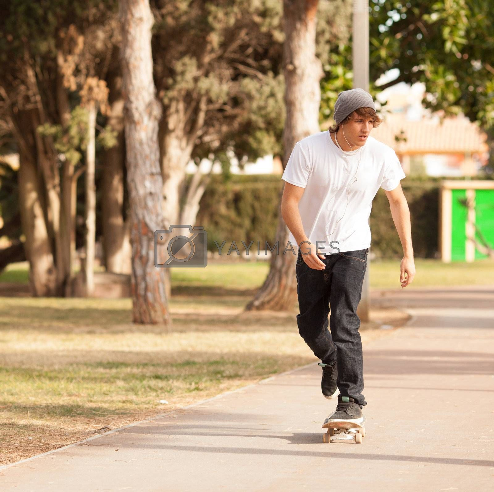 Royalty free image of young skater rolling down the street by Lcrespi