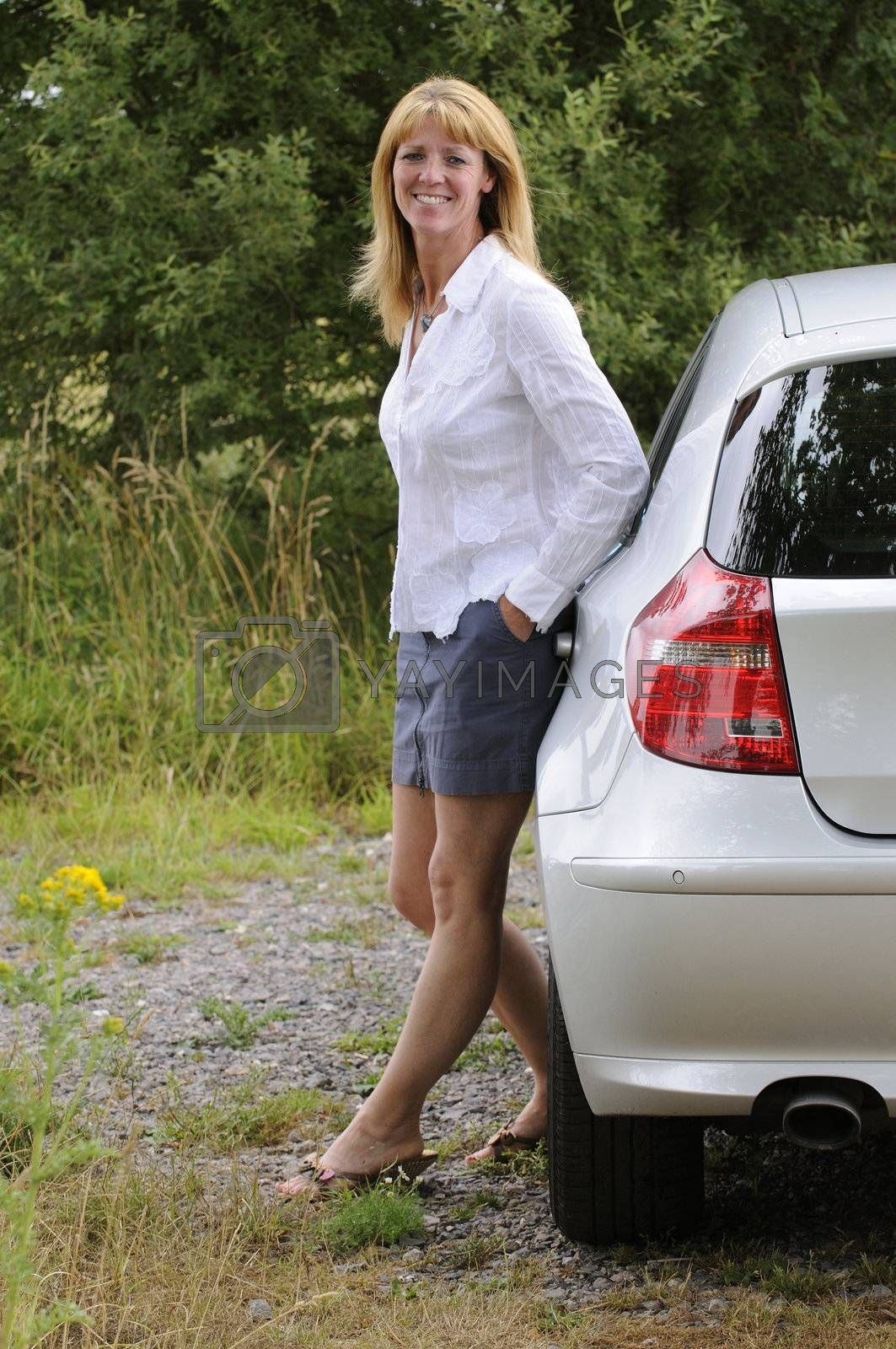 Mature woman wearing a white shirt and skirt leaning on a car