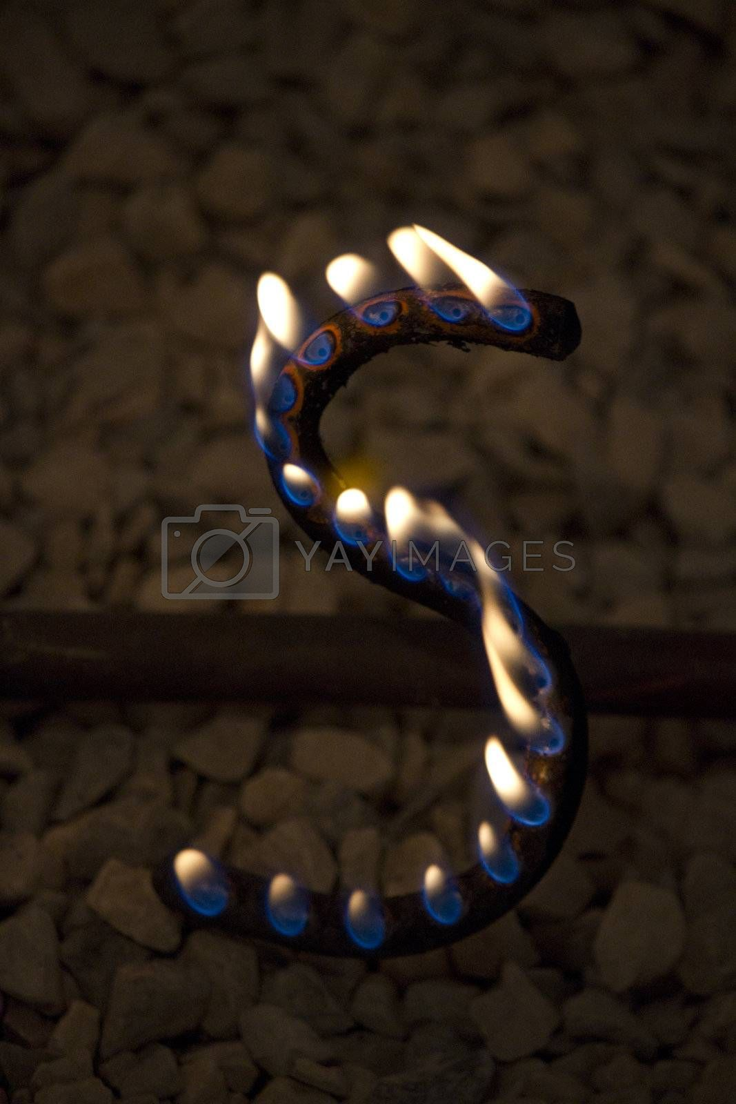 Close up view of an S letter made with iron with fire coming out of holes.