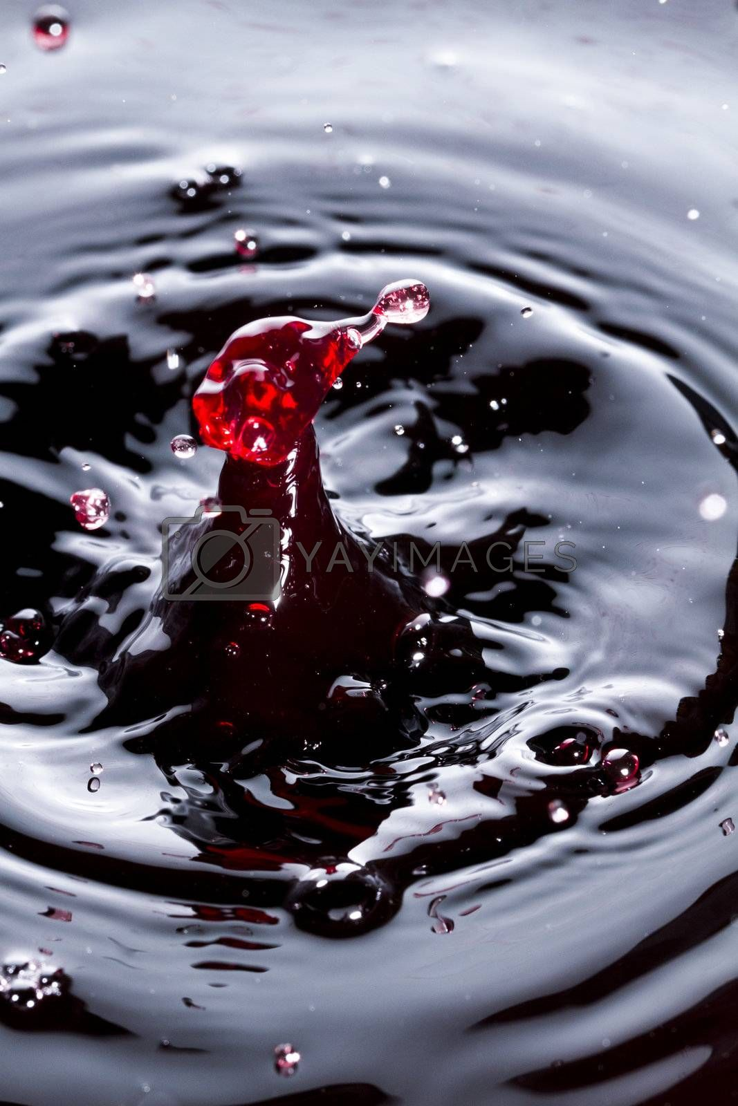 Close view of a droplet of wine hitting a surface of wine.