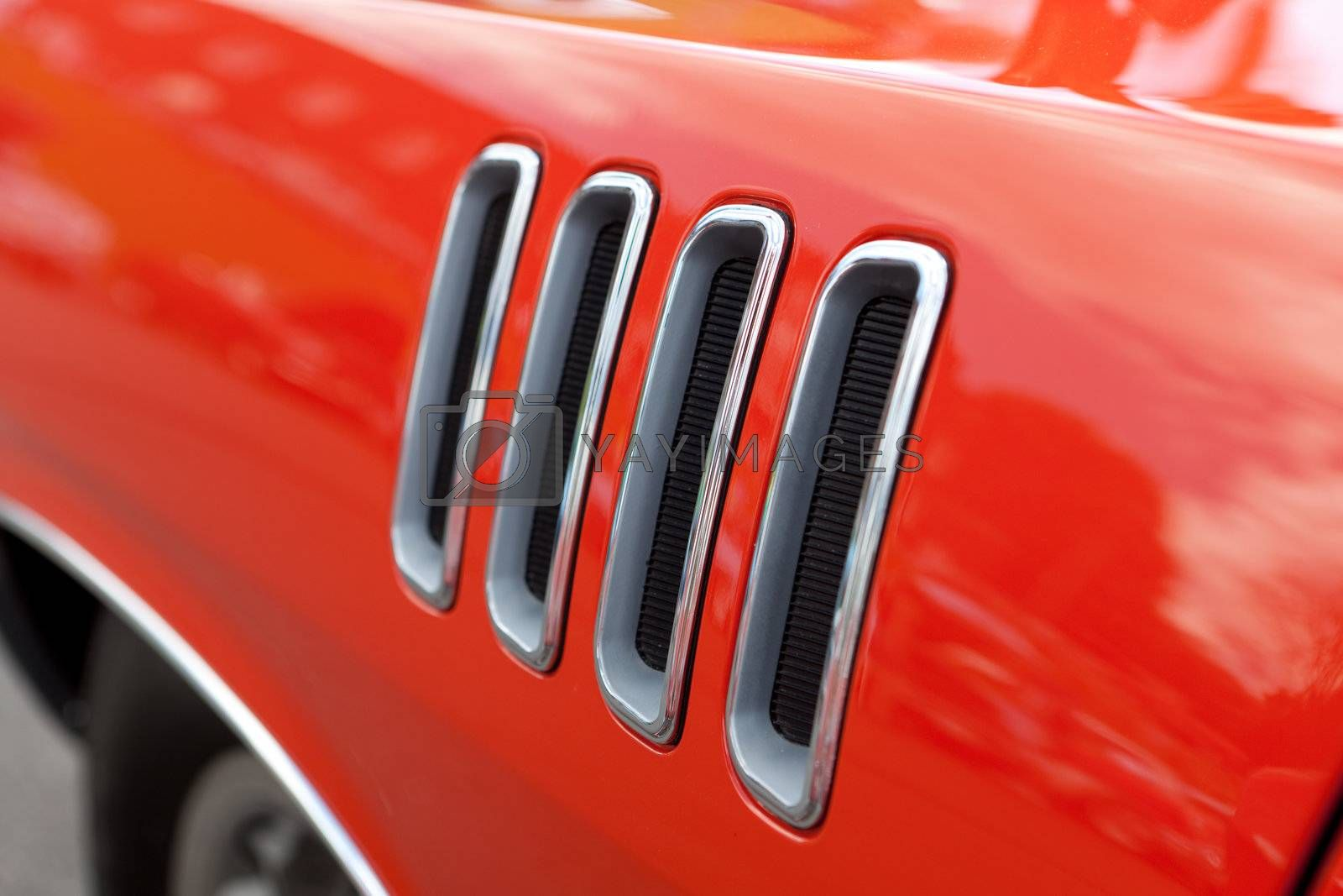 Close up detail of the louvered fender vents on a late model American muscle car with chrome accents.