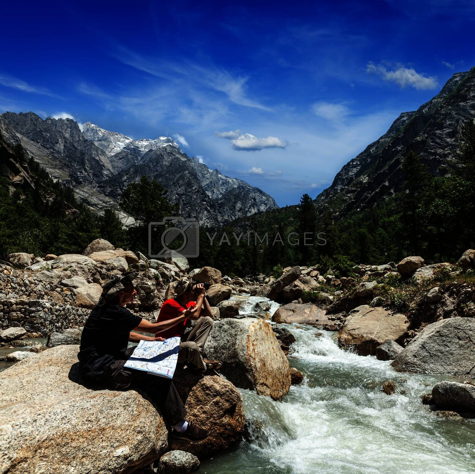 Hiker trekkers read a trekking map on trek in Himalayas mountains. Himachal Pradesh,India