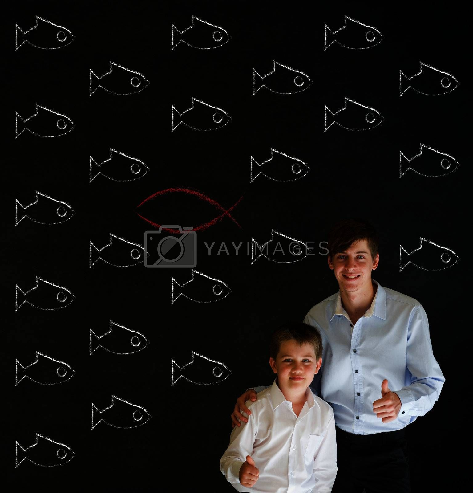 Thumbs up boy dressed up as business man with teacher man and independent thinking Jesus, God, Christianity fish on blackboard background
