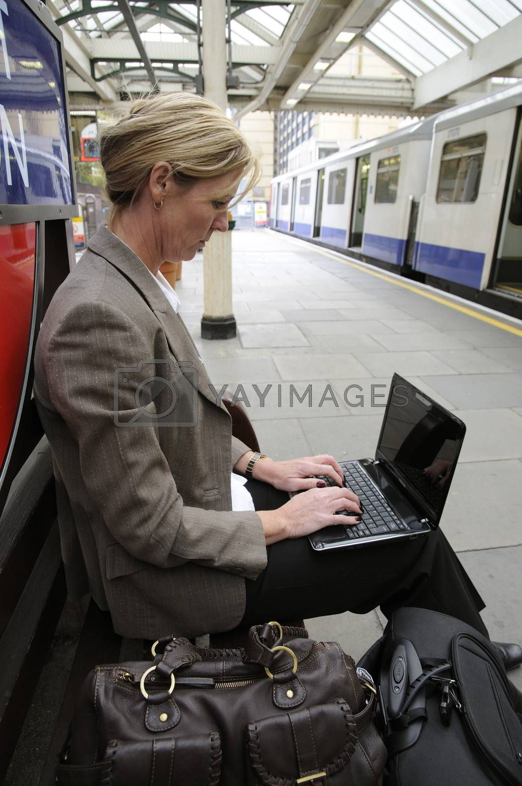 Businesswoman using a netbook computer sitting on a railway station platform