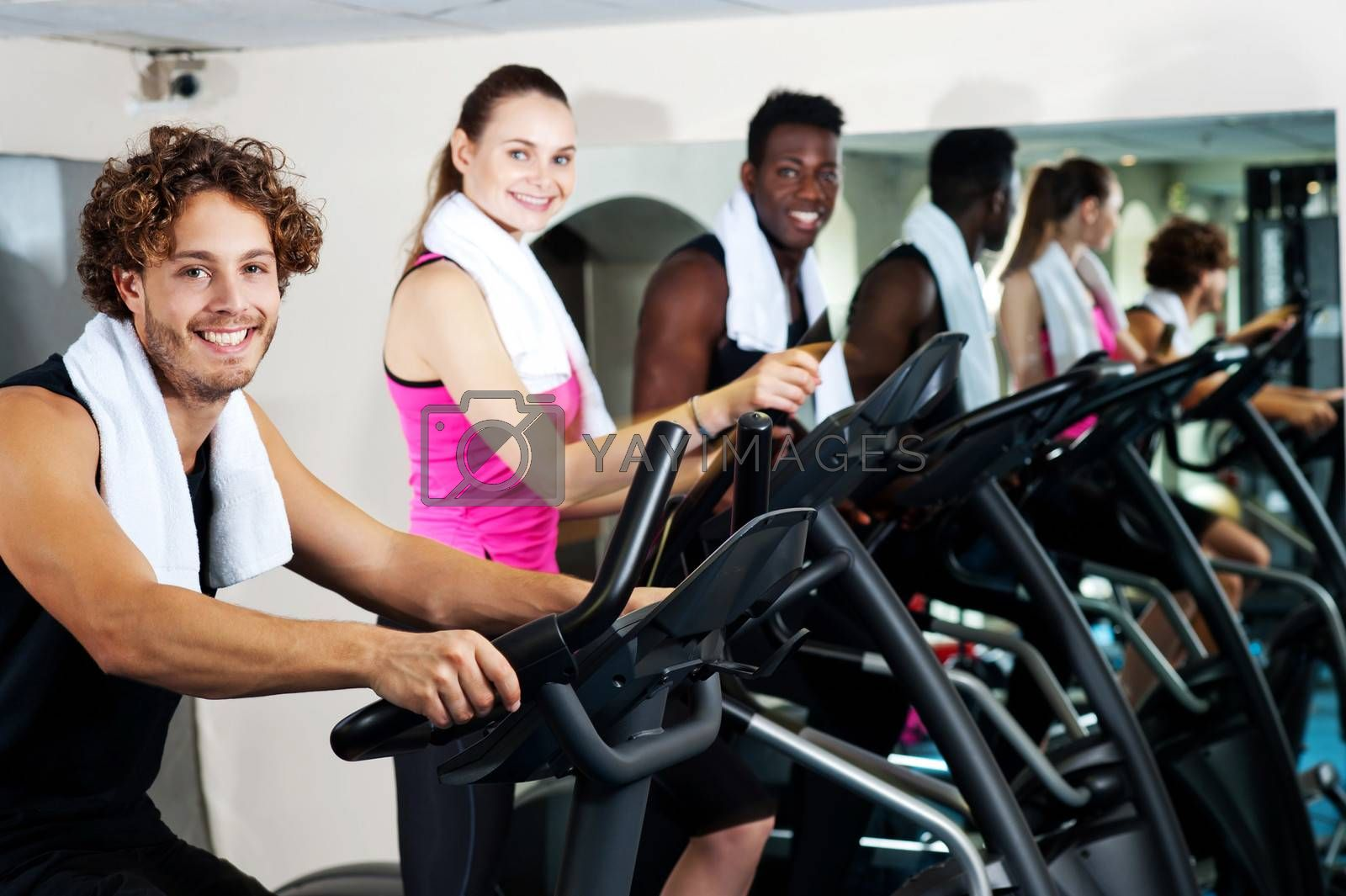 Smiling young people cycling at the fitness centre