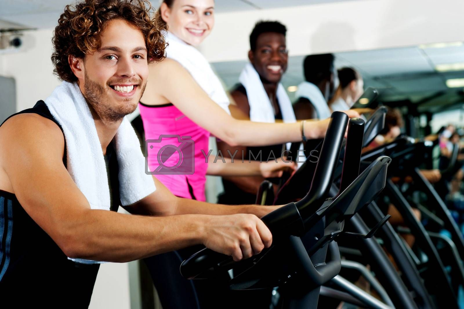 Smiling young people cycling at the fitness center