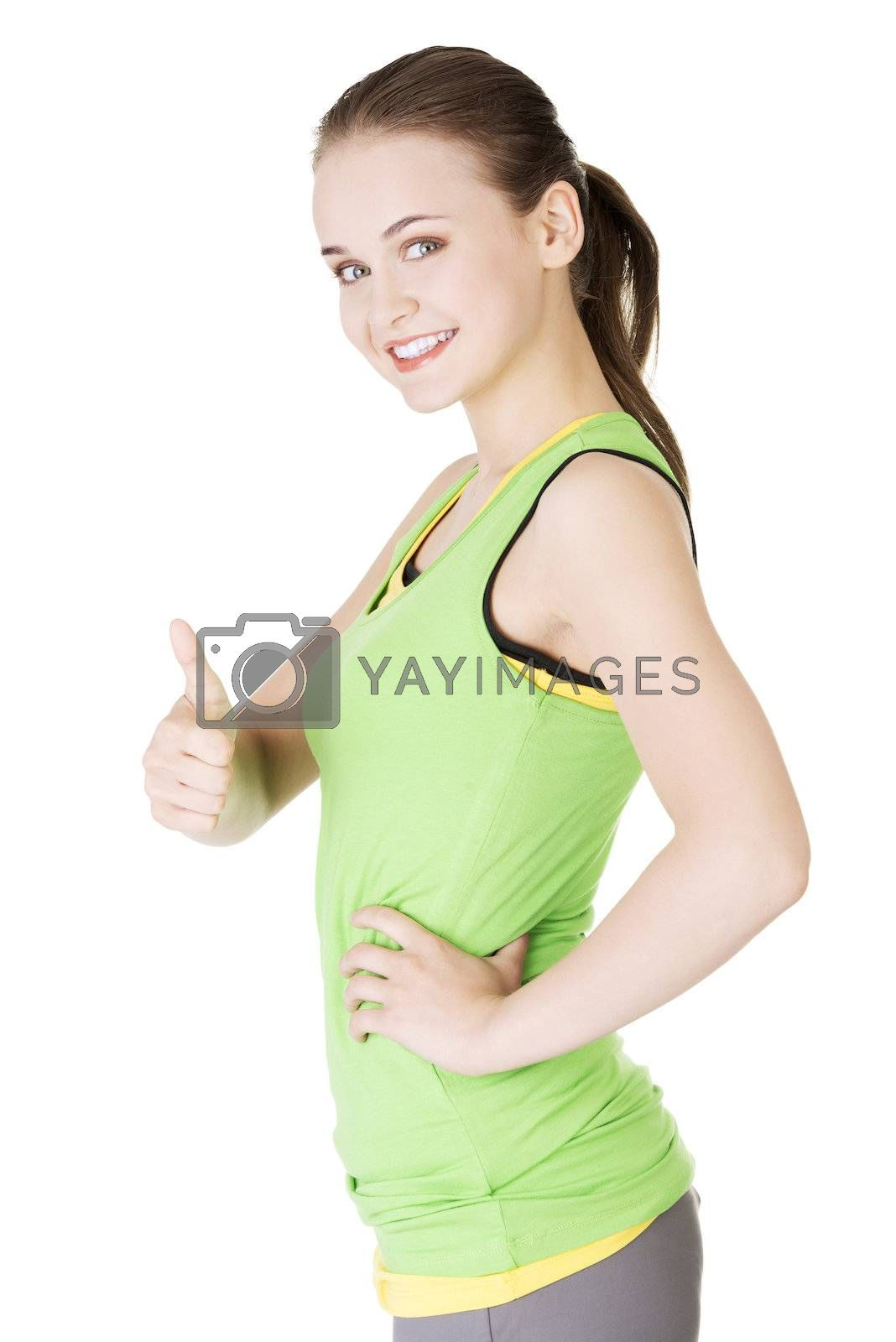 Fitness woman in sport clothes gesturing thumbs up by BDS