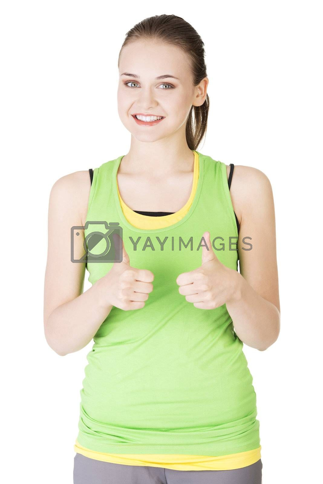 Attractive fitness woman in sport clothes gesturing thumbs up, isolated on white