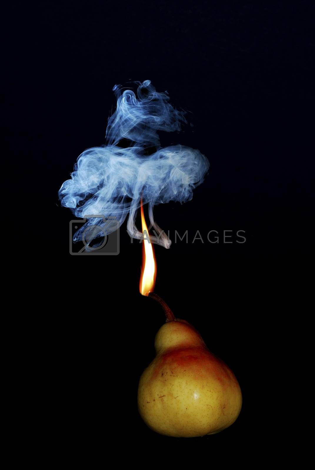 pear portrait with a flame and gray smoke on black background