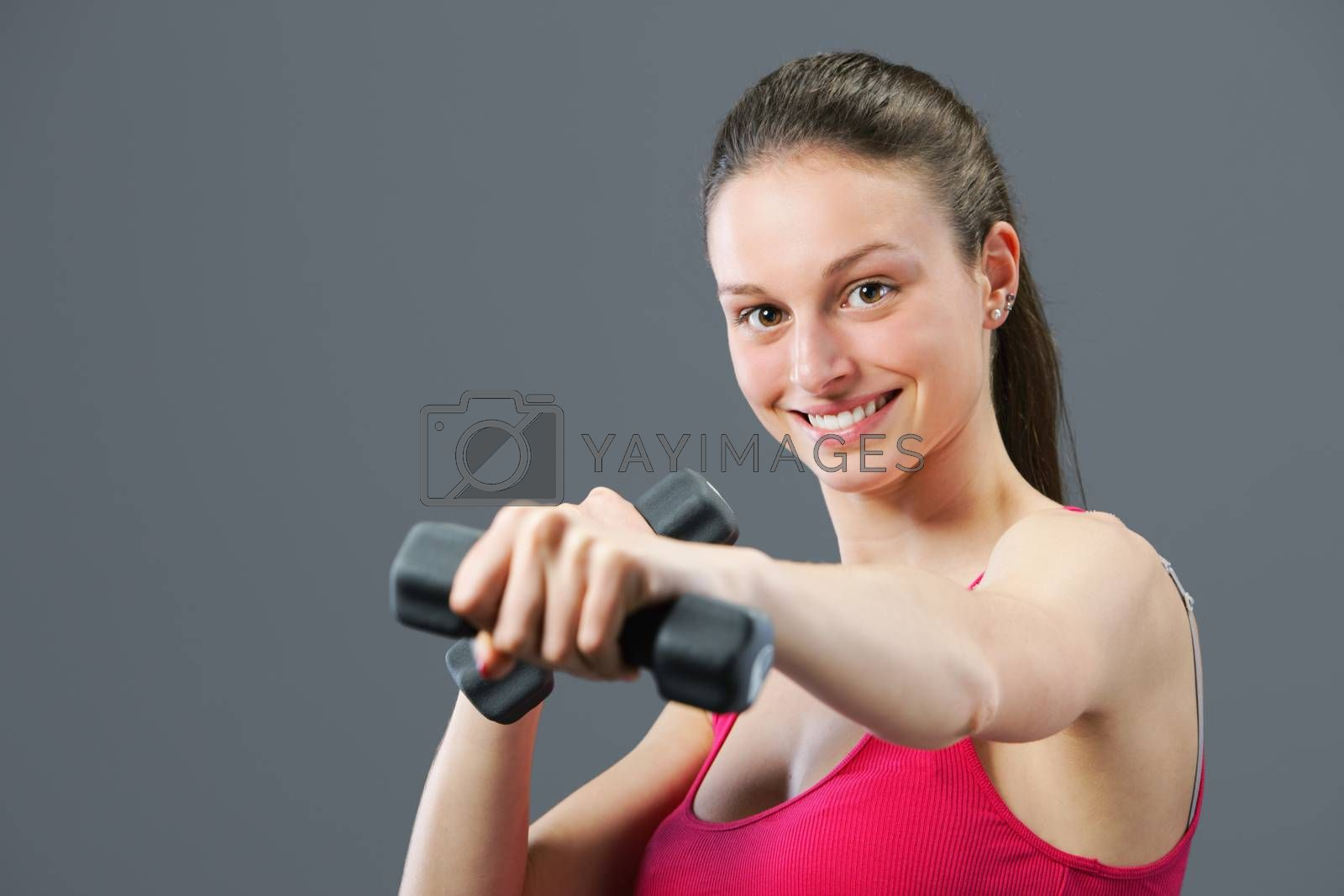 Portrait of beautiful young woman lifting dumbbells during exercise