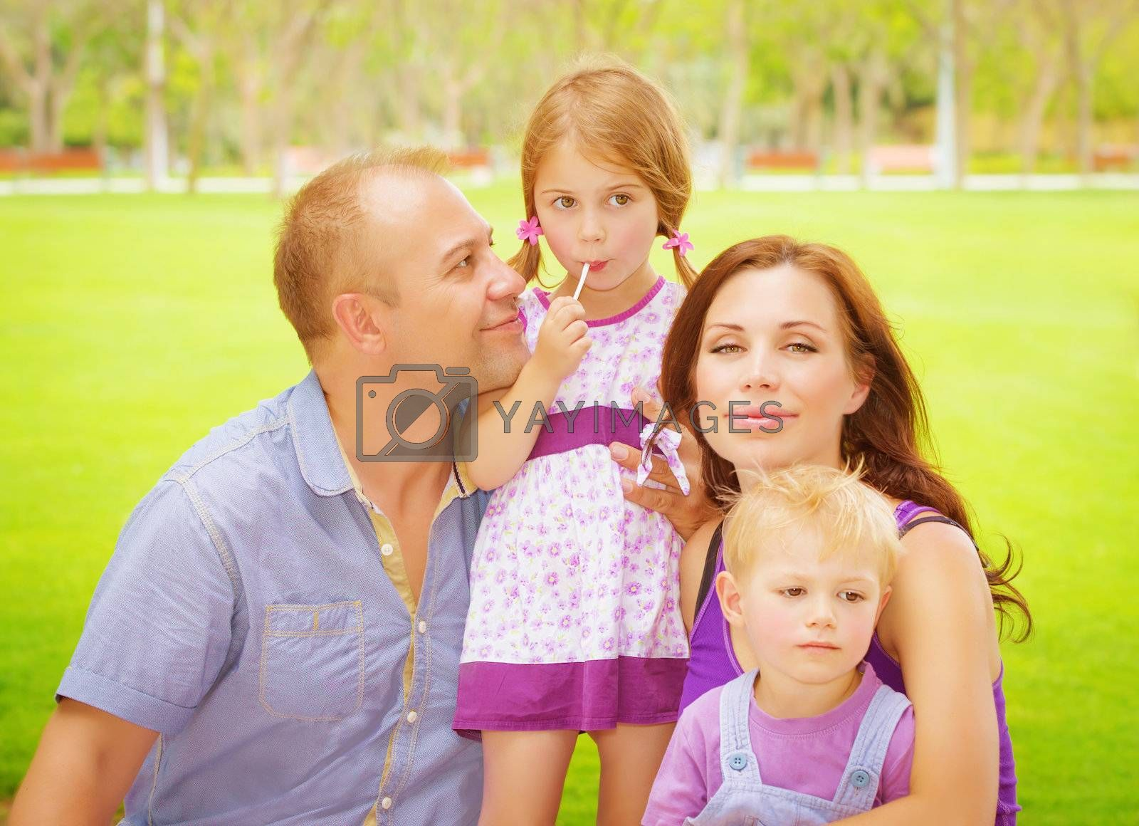Portrait of happy family having fun outdoors, young parents with two cute kids in spring park, spending time together, love concept