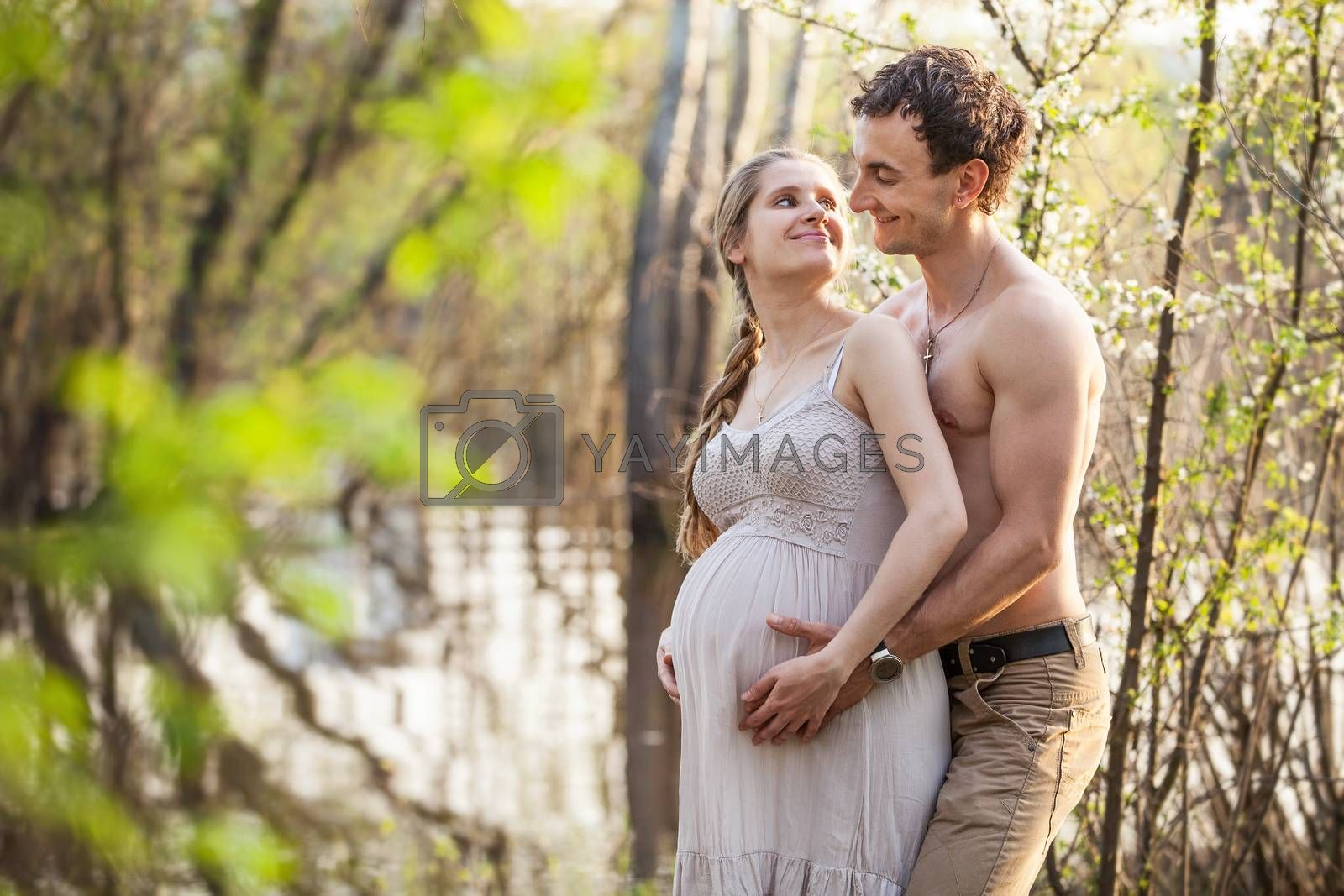 Young pregnant couple at the river in spring