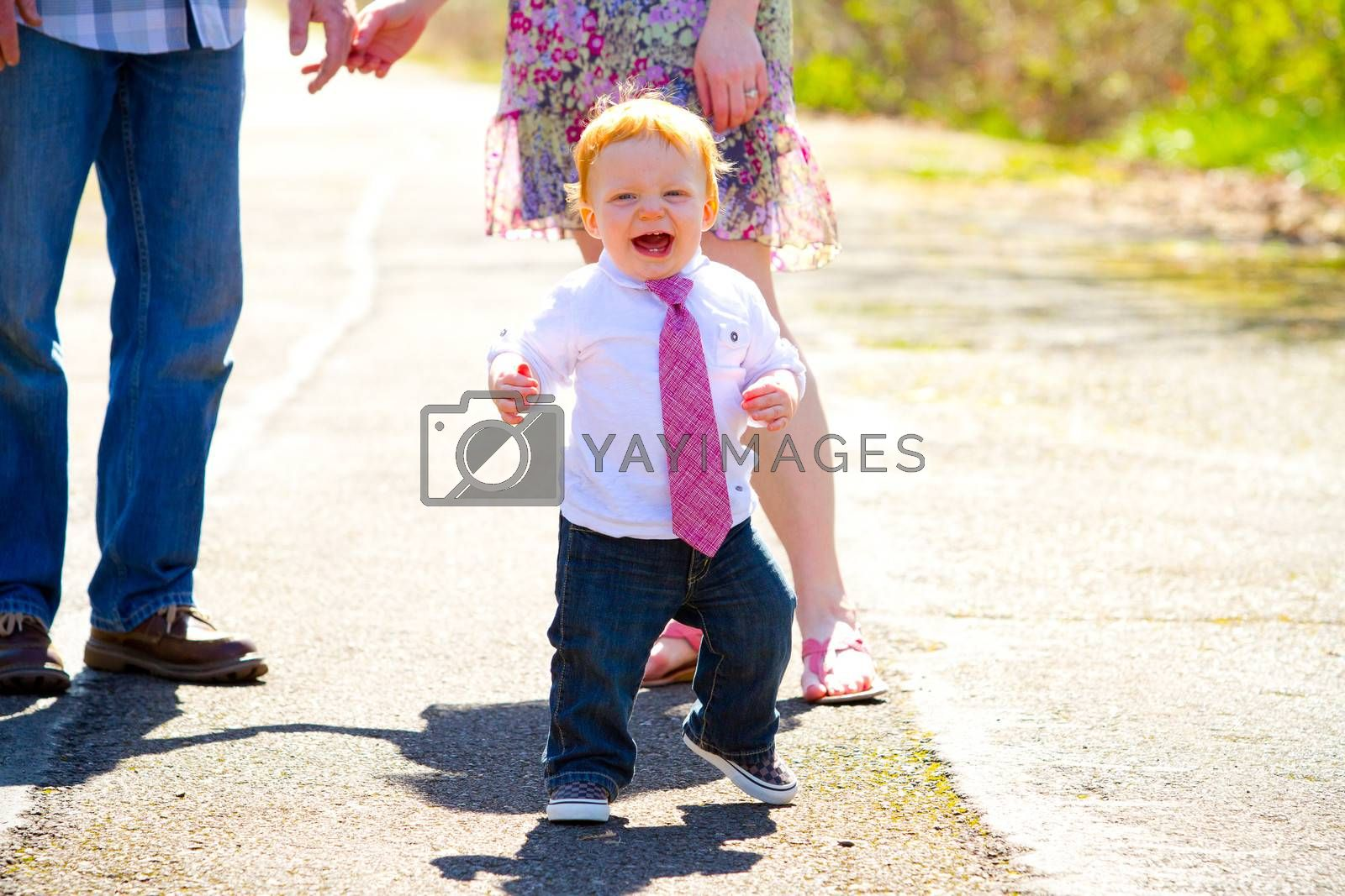 A baby boy runs away from his parents during an outdoor photo shoot with the family.