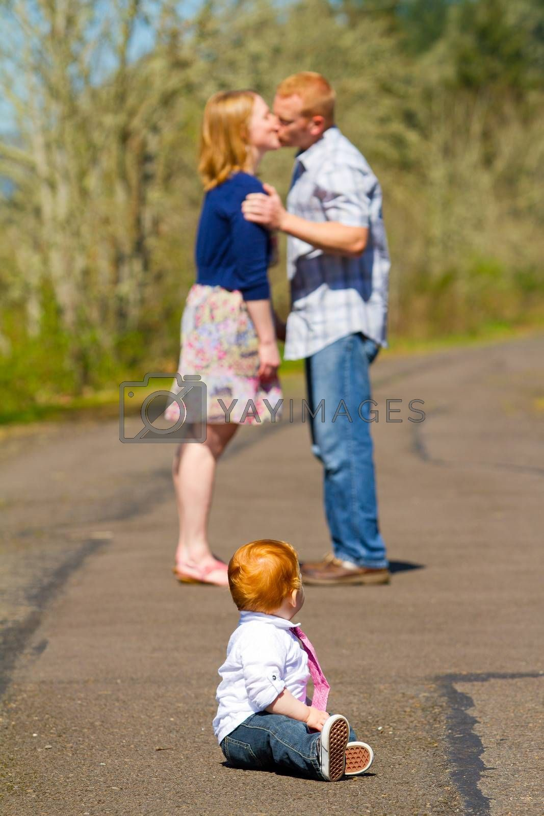 In this selective focus image the parents of a baby one year old boy are kissing out of focus in the background.