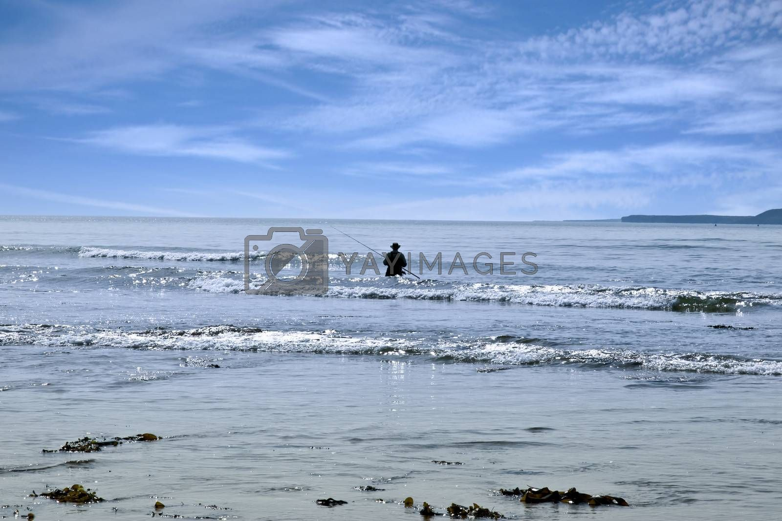 lone man fishing in the river Shannon estuary waves in Ballybunion county Kerry Ireland