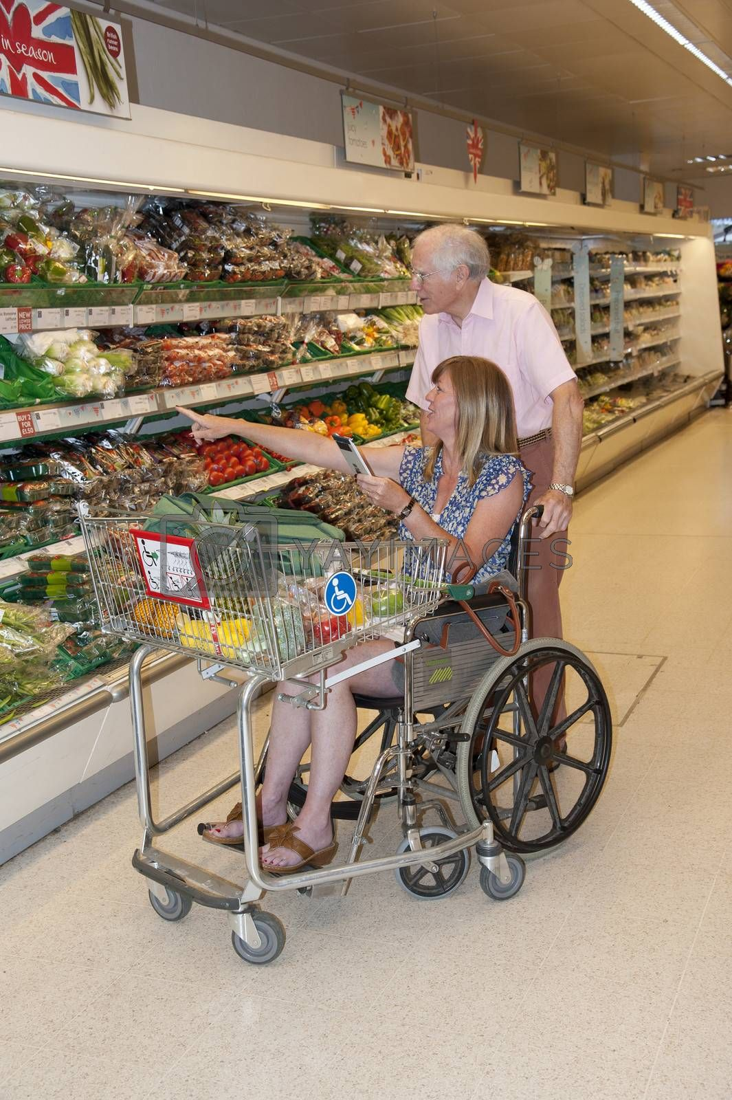 Woman in wheelchair shopping in a supermarket using a disablity trolley being assisted by a male carer