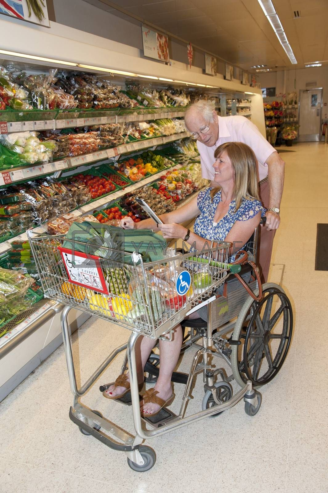 Male carer and woman in wheelchair shopping in a supermarket using a disablity trolley